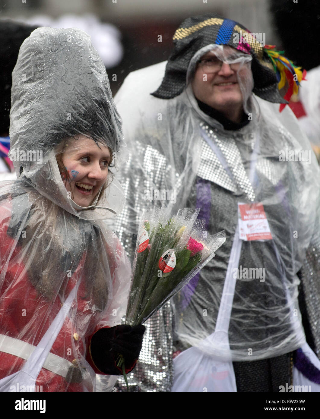 Cologne, Germany. 04th Mar, 2019. Cologne, Germany. 04th Mar, 2019.  Carnivalists use rain ponchos to protect themselves from the rain during the Rose Monday procession. With the Rose Monday processions, the Rhineland street carnival reaches its climax. Photo: Federico Gambarini/dpa Credit: dpa picture alliance/Alamy Live News - Stock Image