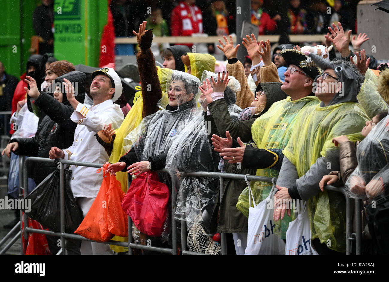 Cologne, Germany. 04th Mar, 2019. Cologne, Germany. 04th Mar, 2019.  Spectators protect themselves on the edge of the Rose Monday procession with umbrellas and plastic ponchos against a shower. With the Rose Monday processions, the Rhineland street carnival reaches its climax. Photo: Henning Kaiser/dpa Credit: dpa picture alliance/Alamy Live News - Stock Image