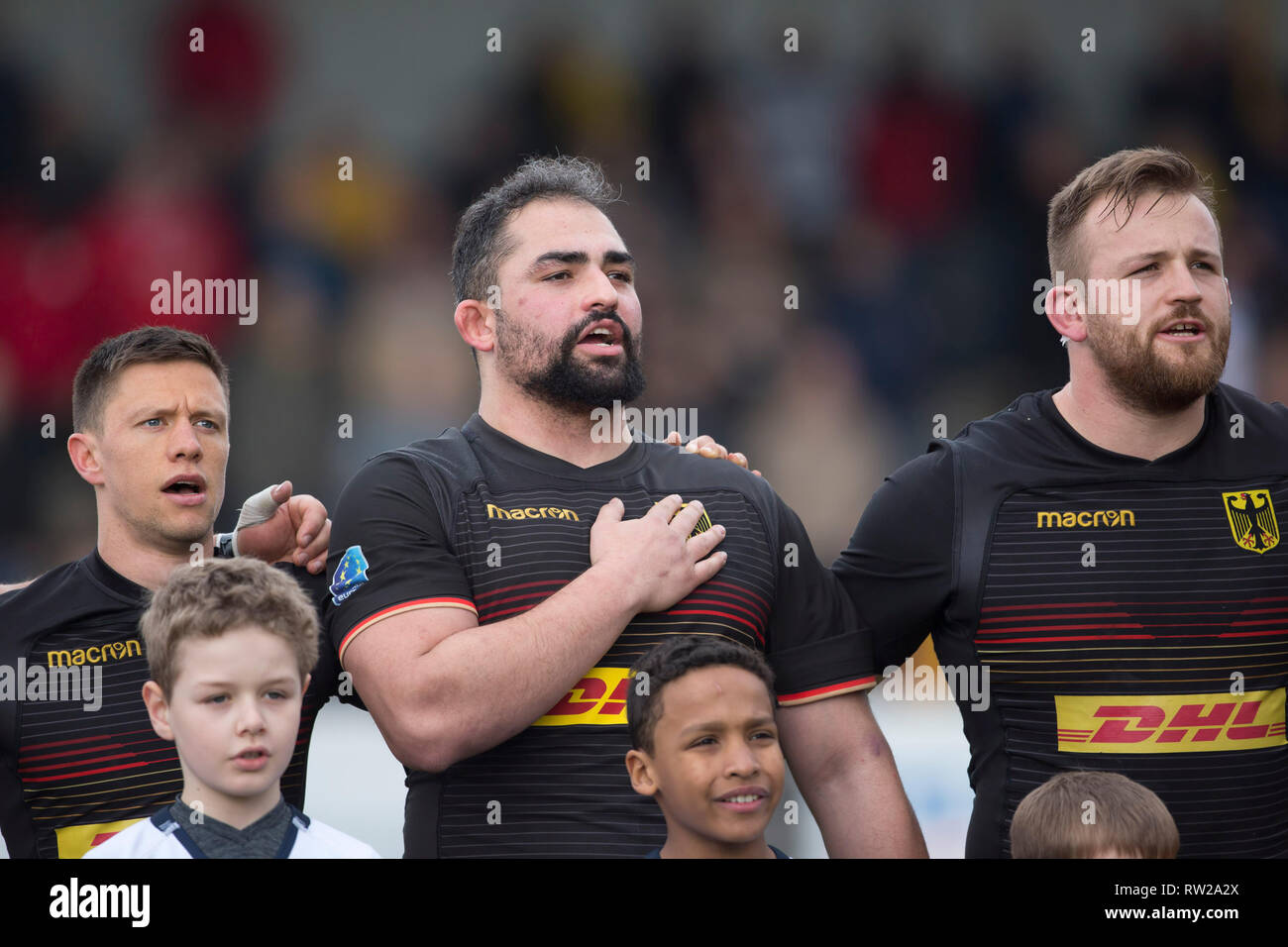 Heidelberg, Germany. 02nd Mar, 2019. Third match of the Rugby Europe Championship 2019: Germany-Russia on 09.02.2019 in Heidelberg. In the middle of the picture Samy Fuechsel (Germany, 3) sings the national anthem full of fervor. Left Tim Menzel (Germany, 9), right Joern Schroeder (Germany, 4). Credit: Jürgen Kessler/dpa/Alamy Live News - Stock Image