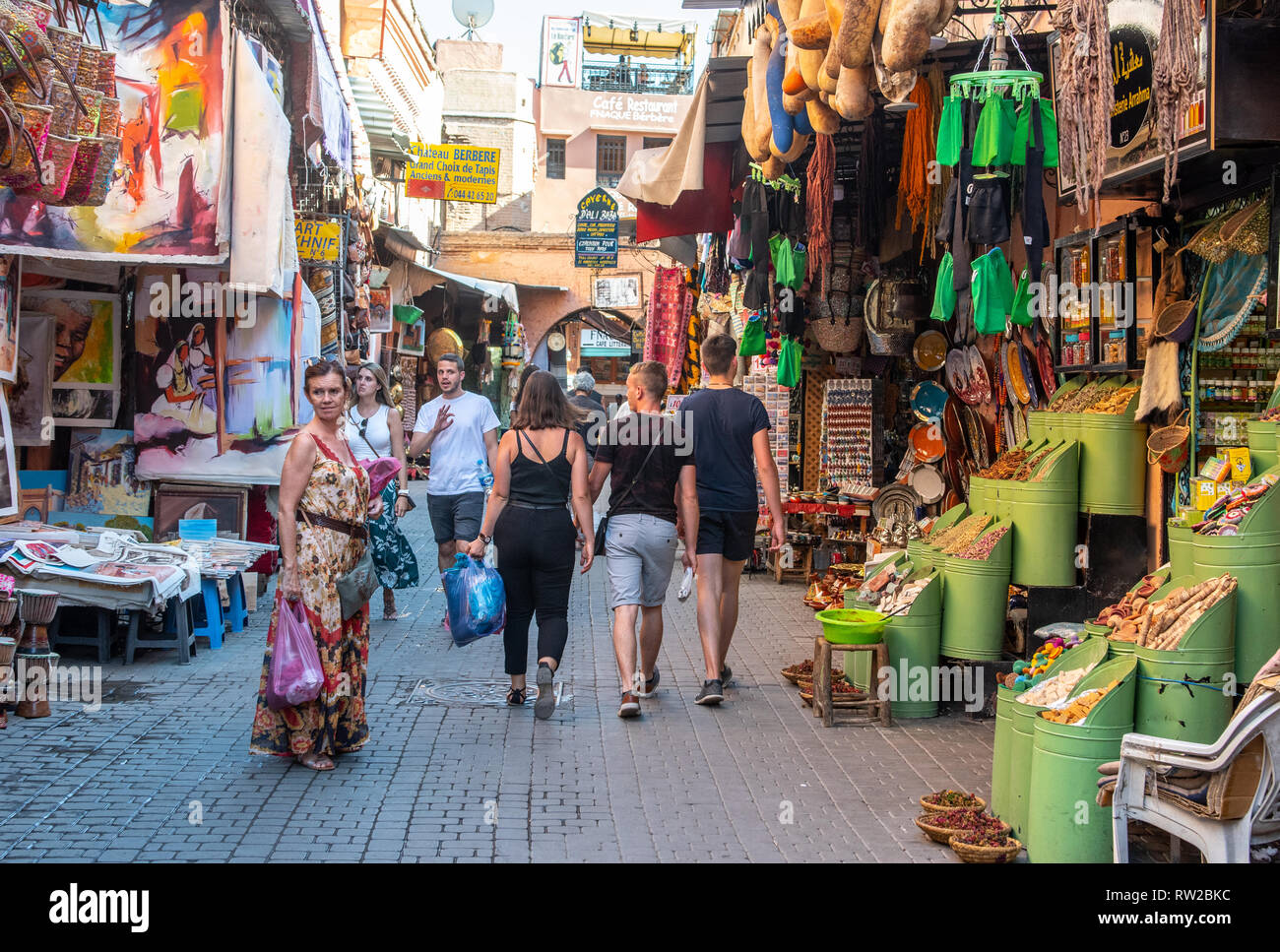 Shoppers wander down narrow street in medina quarter of Marrekech lined with market stalls selling art, spices, and other goods, Morocco - Stock Image