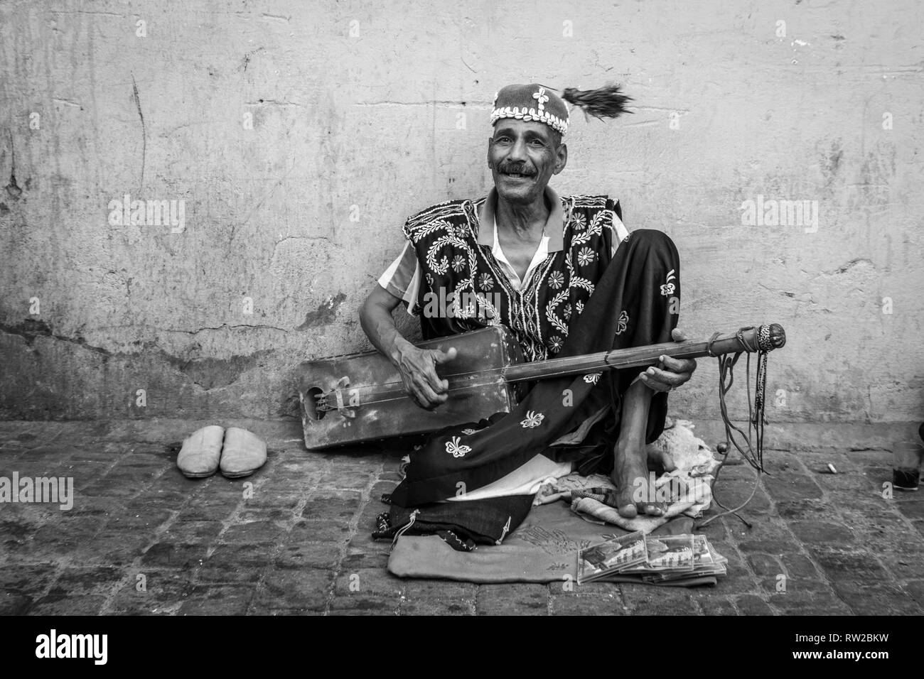 Man spins tassle of his fez around busking with his sintir on the streets of Marrekech, Morocco - Stock Image
