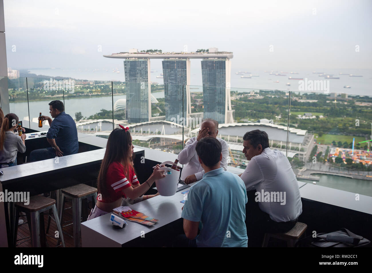 28.12.2018, Singapore, Republic of Singapore, Asia - Guests at the Empire Sky Lounge with the Marina Bay Sands Hotel in the backdrop. - Stock Image
