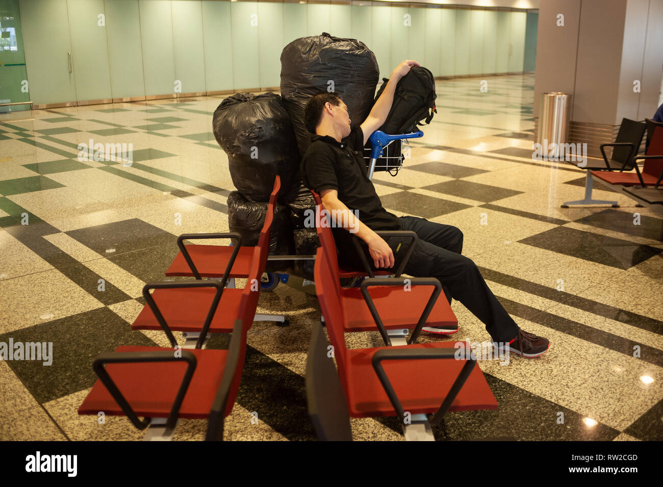 01.03.2019, Singapore, Republic of Singapore, Asia - A passenger is sleeping next to his luggage in a public area at Singapore's Changi Airport. - Stock Image