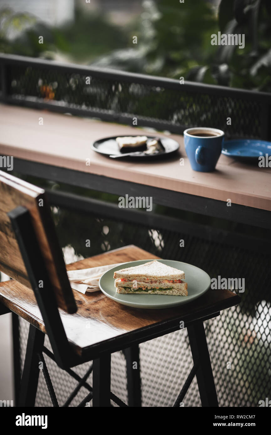 Abstract scene of breakfast meal set including tuna sandwich, hot long black coffee, and brownie cheese cake on outdoor wood bar. Weekend morning acti - Stock Image