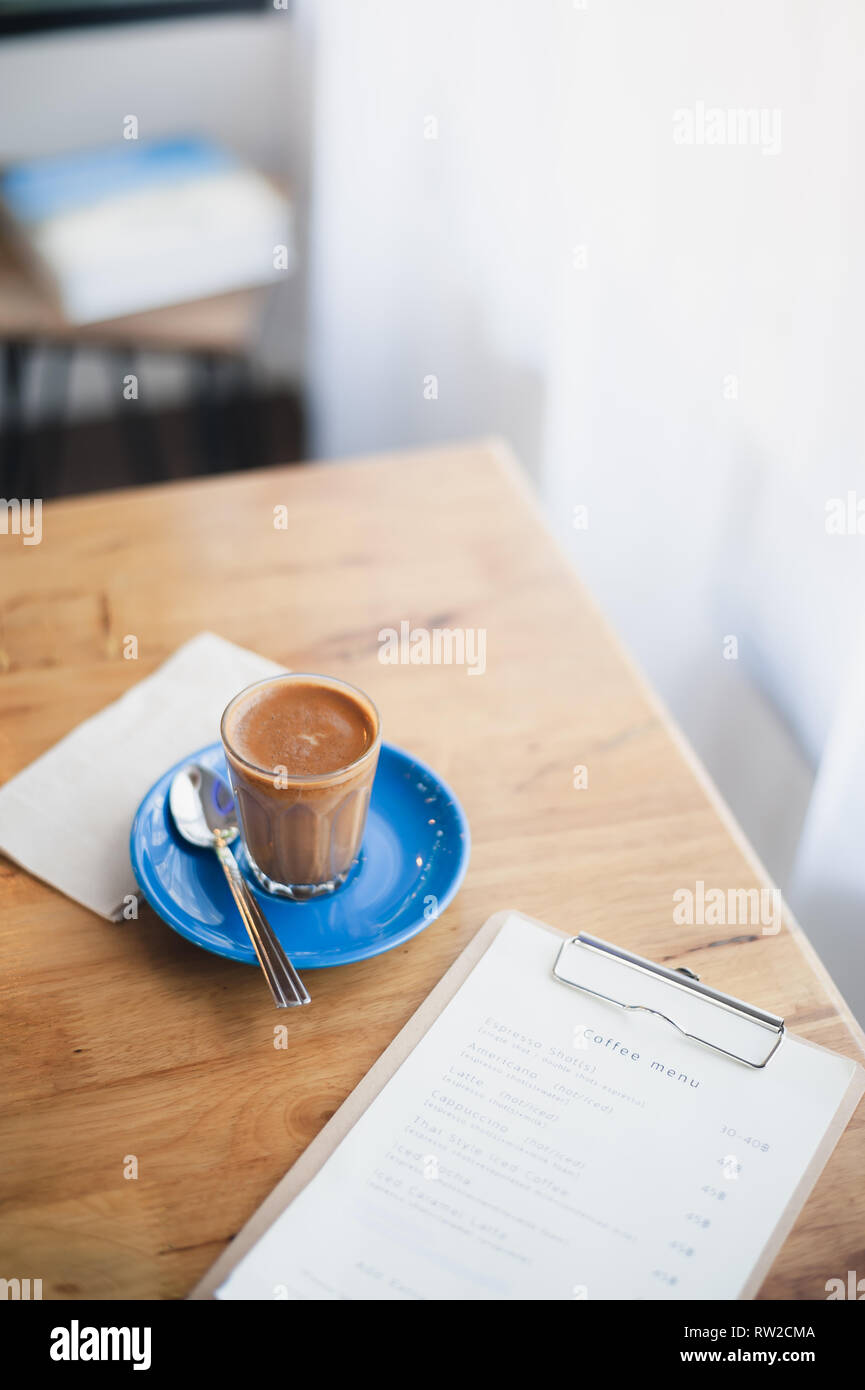 Abstract emotional scene of hot Piccolo latte in small coffee glass on table at cafe in morning time. Weekend activity and relaxation. favorite bevera - Stock Image