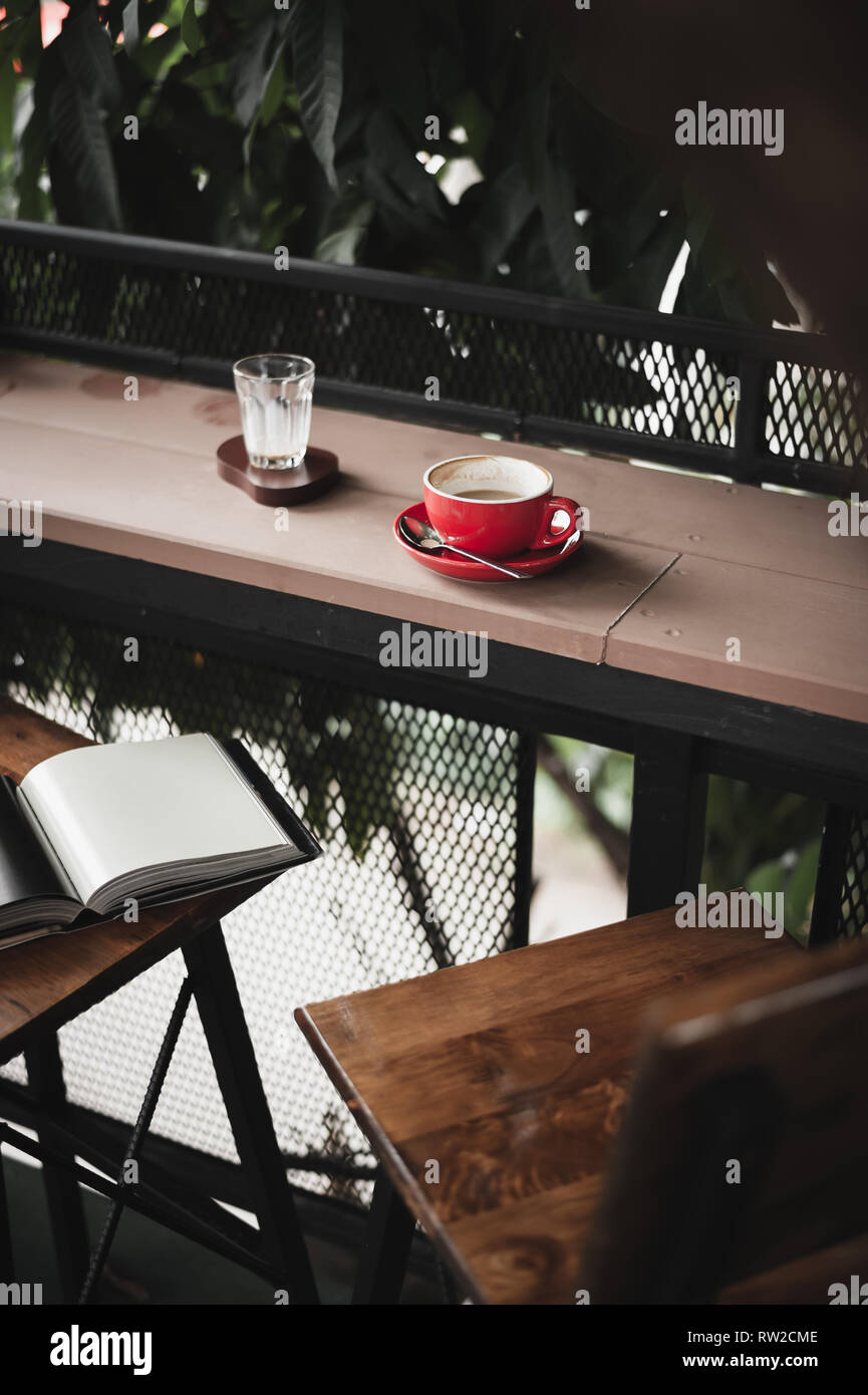 Abstract emotional scene of hot coffe in red coffee cup on table at cafe in morning time. Weekend activity and relaxation. favorite beverage concept o - Stock Image