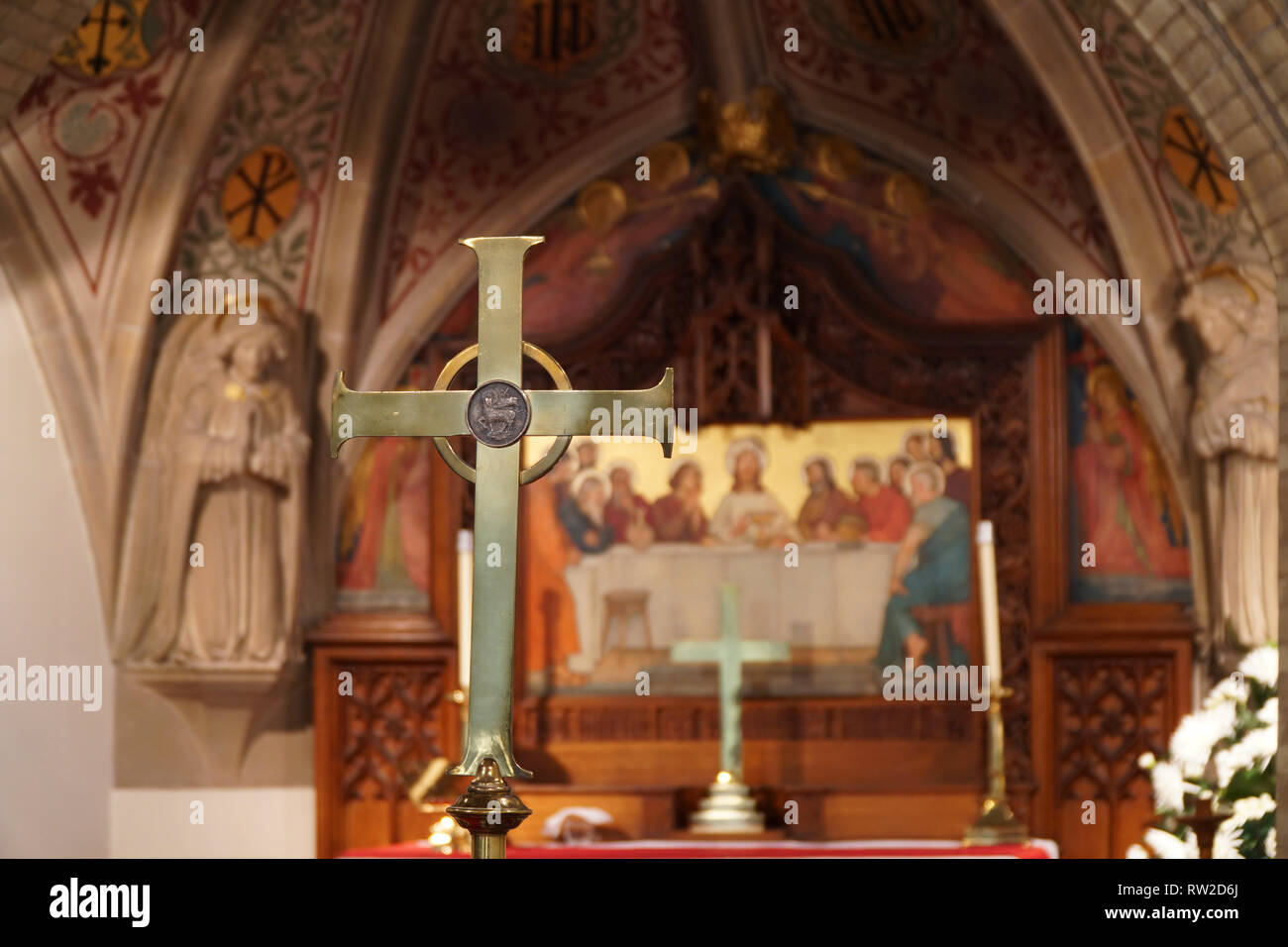 Brass cross in fornt of the high altar in a church with a paiting of the Last Supper in the background - Stock Image