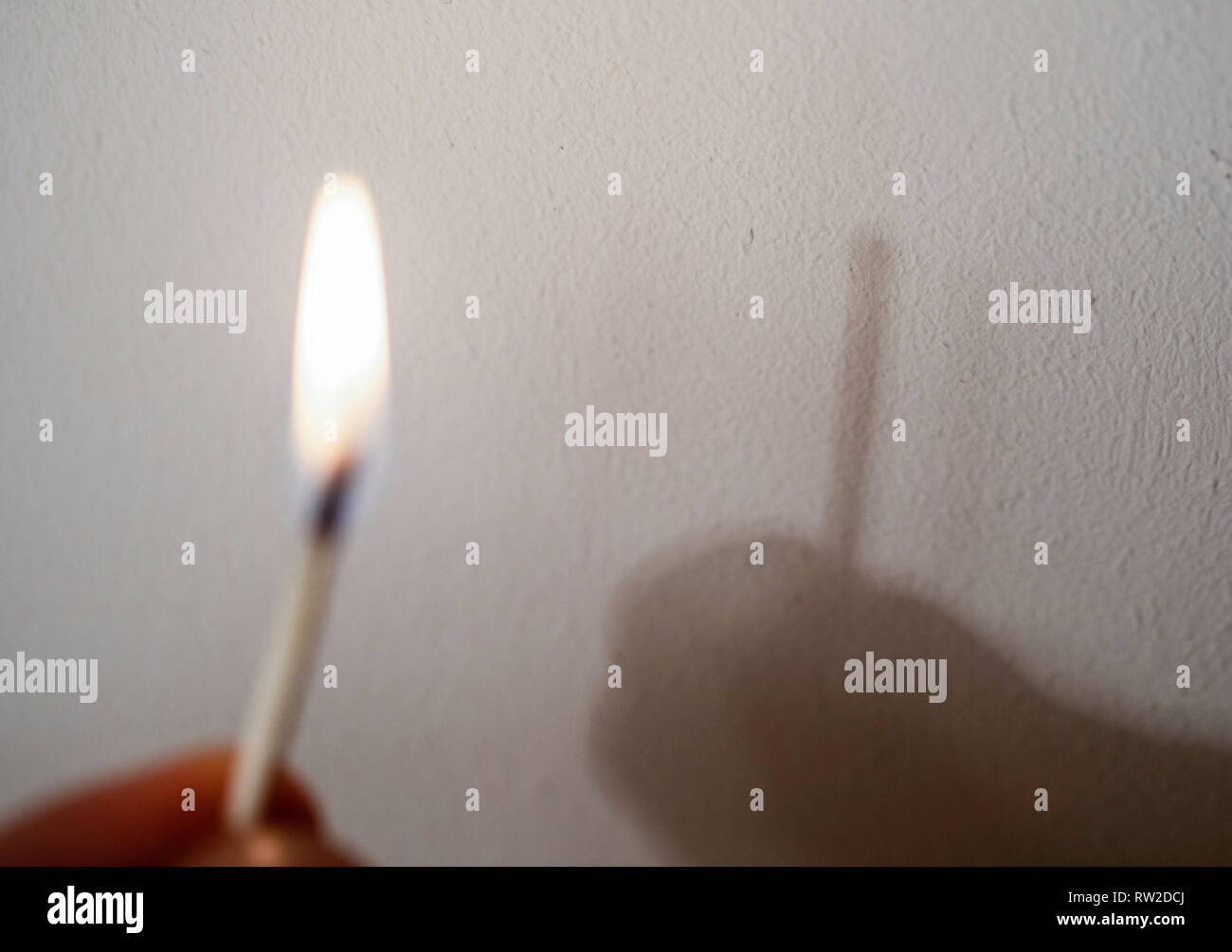 Fire match not throwing a shadow. Play of light and shade Experiment - optical illusion. - Stock Image