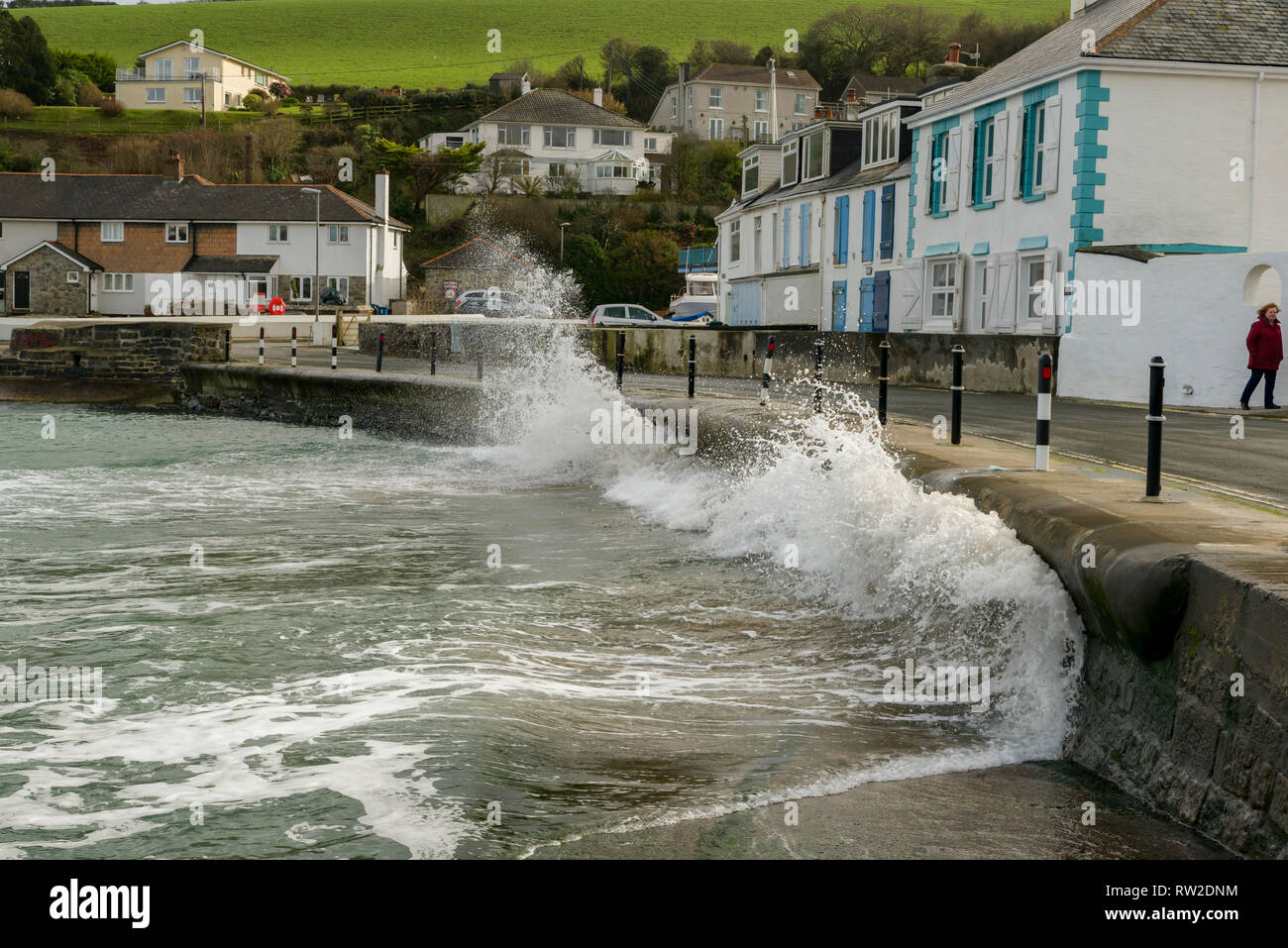 Editorial: People & Logos. Portmellon, Mevagissey, Cornwall, UK. 03/03/2019. Large swells kicked up by storm Freya crash against the sea defences. Stock Photo