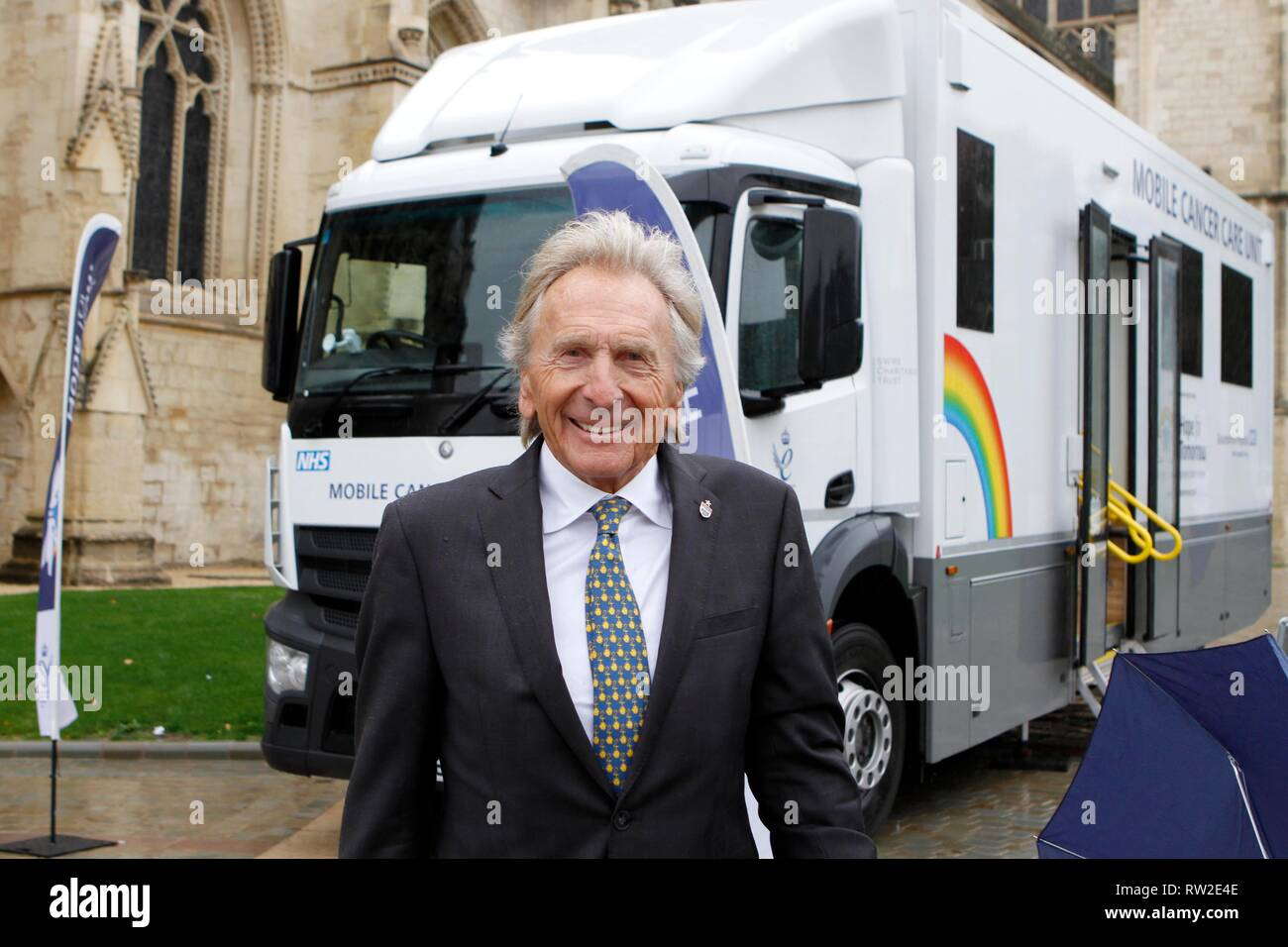 Derek Bell MBE, the hugely successful racing driver, with one of the charity's Mobile Cancer Care Units, parked outside Gloucester Cathedral for the s - Stock Image