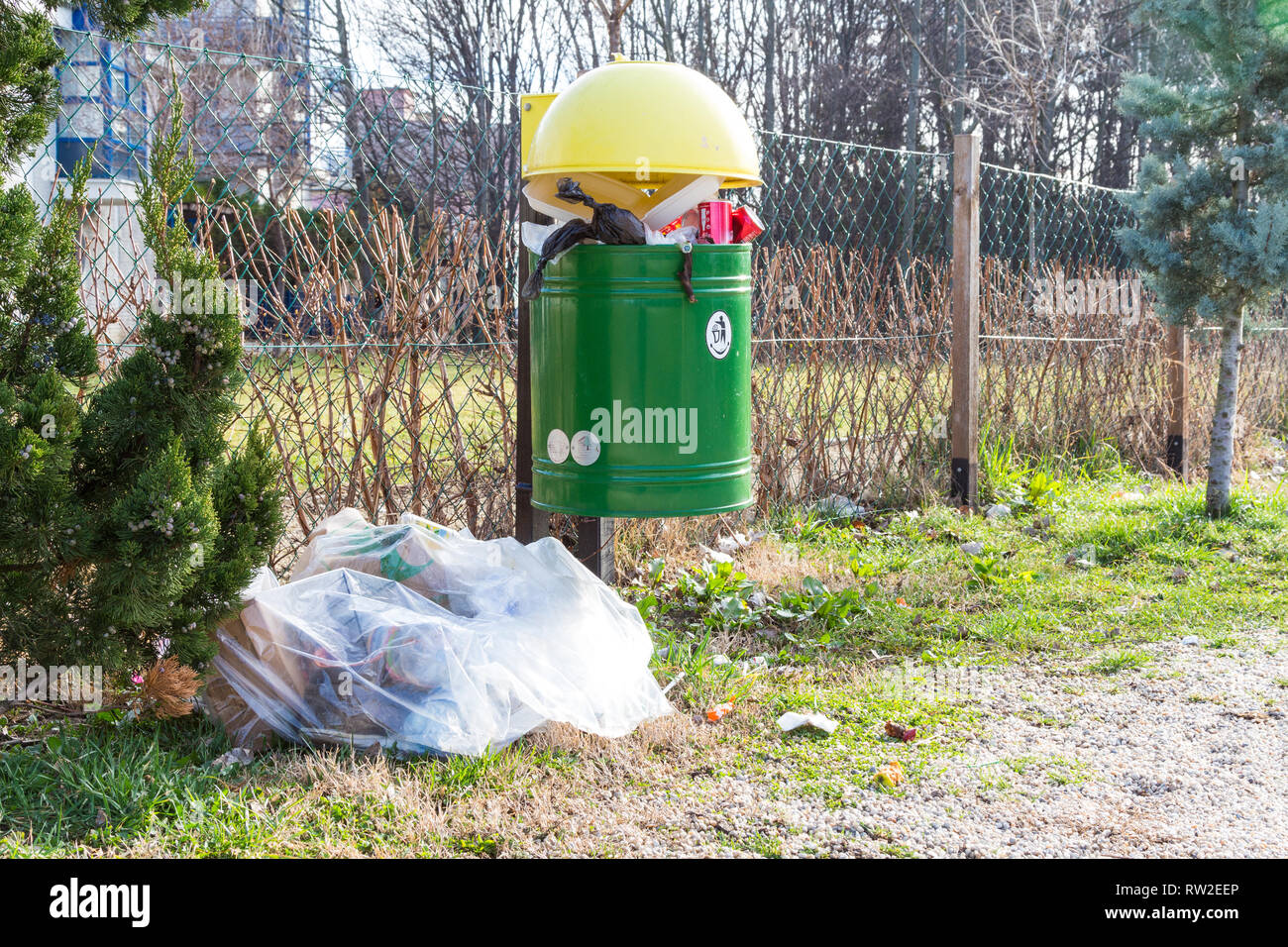Trash bin full of garbage with a bag of rubbish next to it on playground - Stock Image