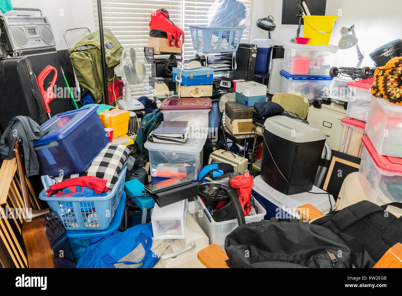 Hoarder room packed with stored boxes, electronics, files, business equipment and household items. - Stock Image