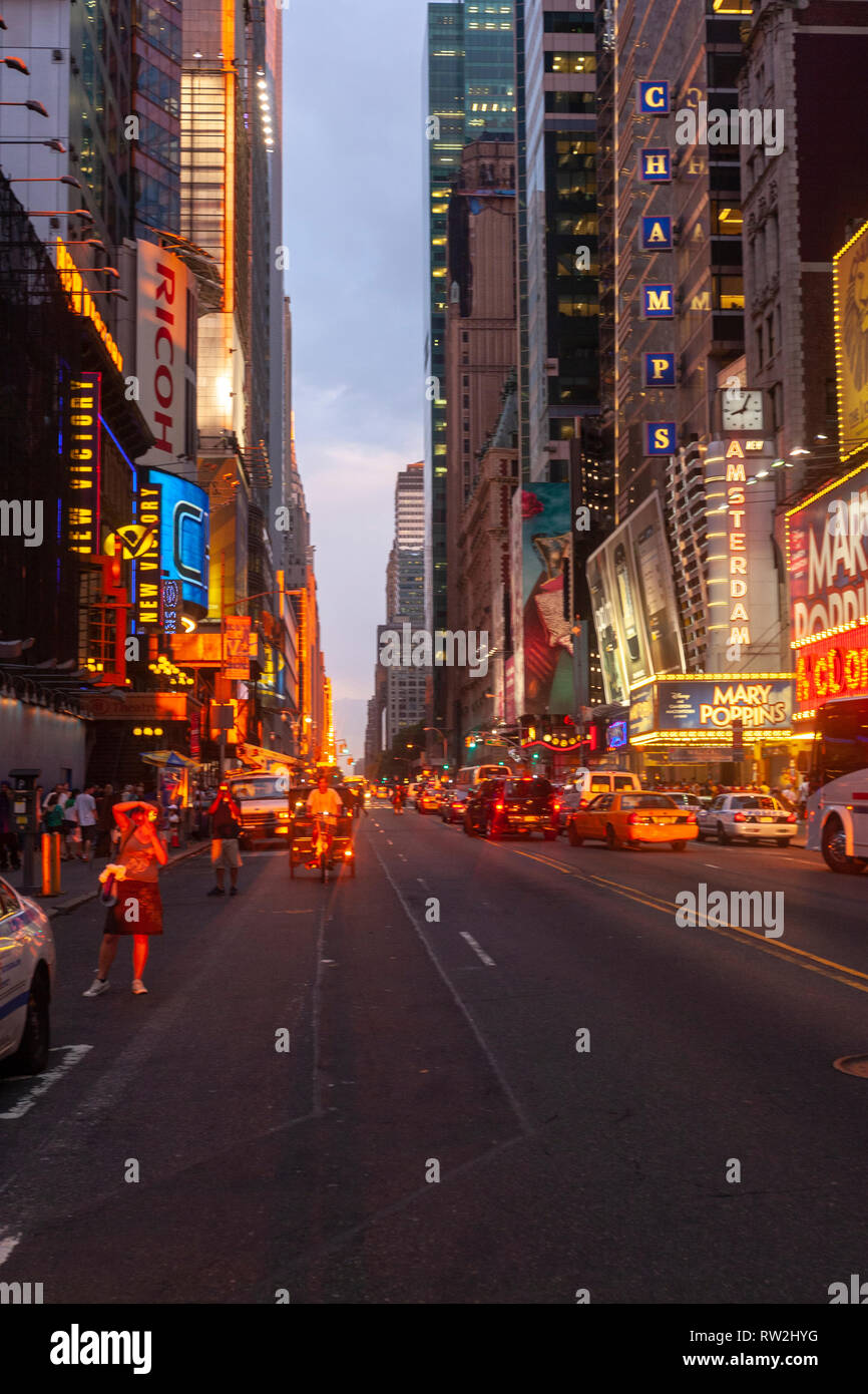 Man taking pictures to the sunset in W 42nd St at sunset near Times Sq, Manhattan, New York City, USA - Stock Image