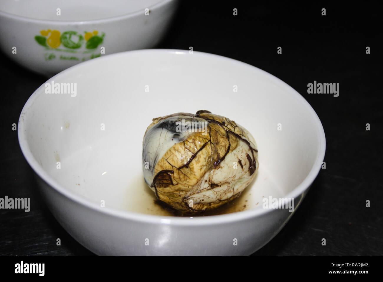 Fetal Duck Egg Balut in a white bowl, Vietnamese cuisine - Stock Image
