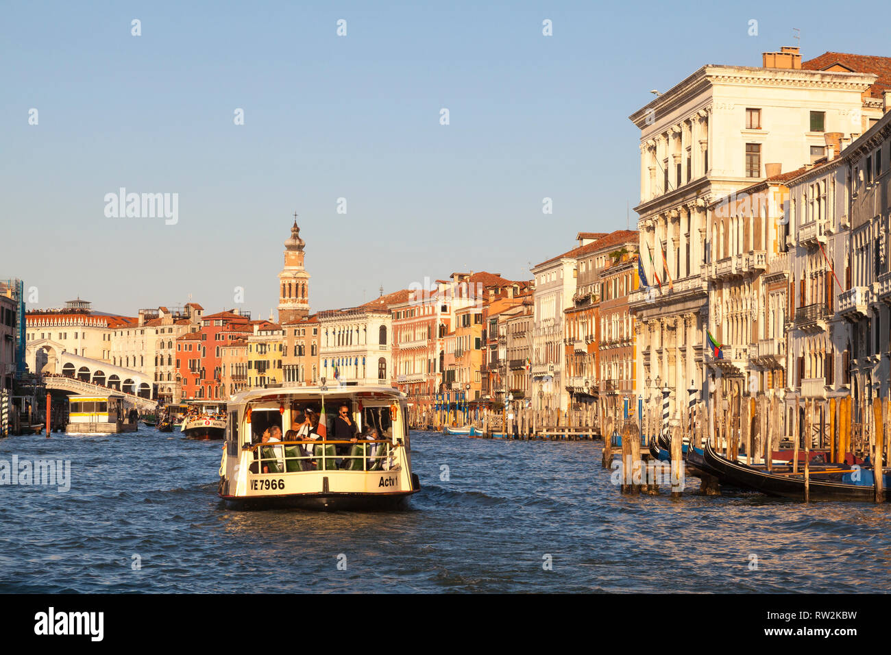 Vaporetto waterbus on the Grand Canal at sunset, Venice, Veneto, Italy with a view past ancient palazzos, palaces, to the Rialto Bridge - Stock Image