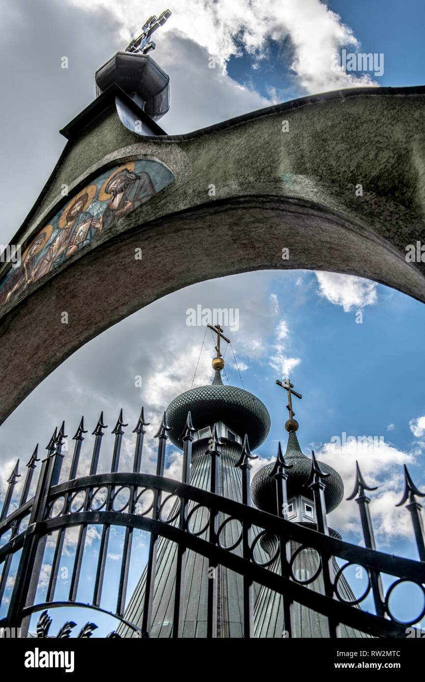 High angle view of closed iron gate with stone archway depicting Christian religious icons in front of Sabor Sviatoj Trojcy, Orthodox church, Hajn—wka - Stock Image
