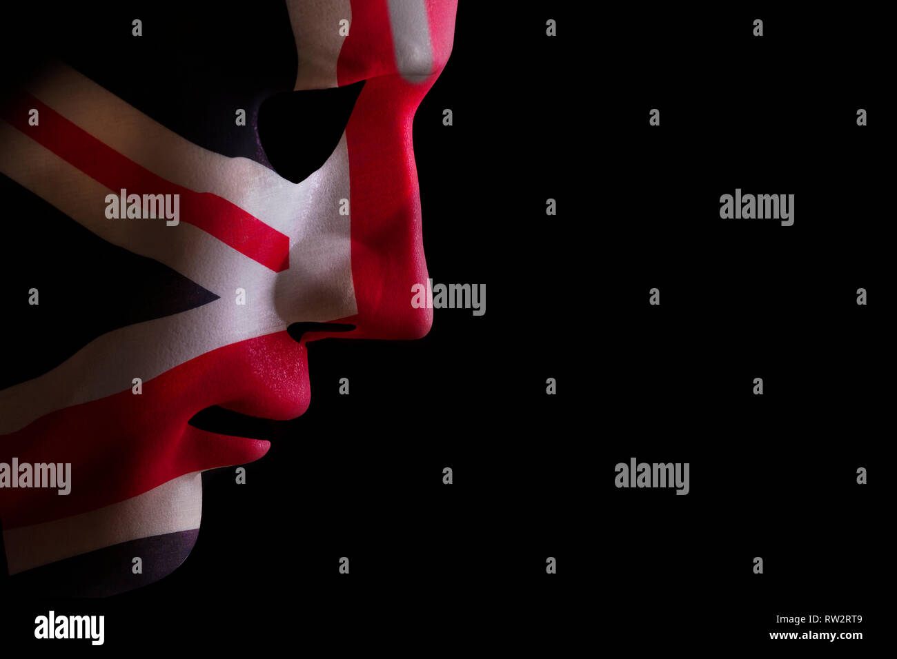 Face mask profile with a union jack flag texture looking down on a black blackground. Space for text - Stock Image