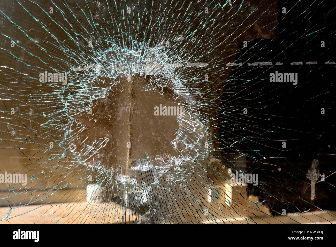 Smashed and broken window in unoccupied high street shop premises a sign of the demise High Street shopping. - Stock Image