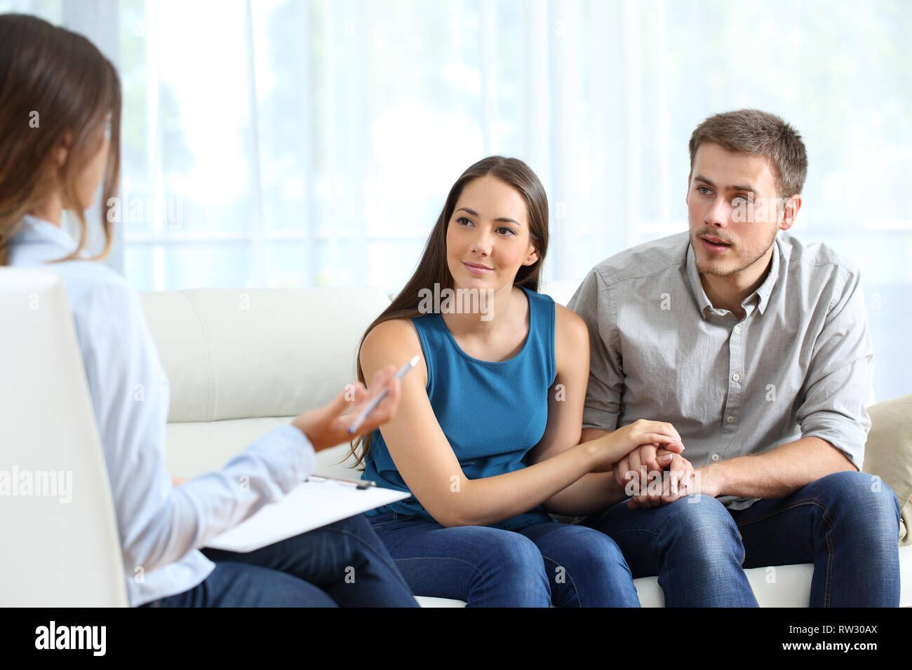 Attentive marriage during a couple therapy sitting on a couch at home or consultation - Stock Image