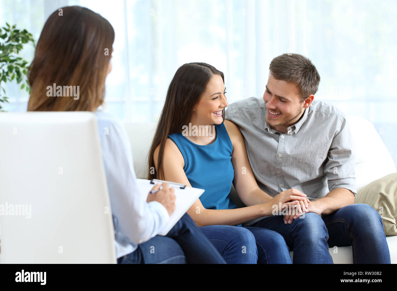 Happy marriage after couple therapy sitting on a couch at home or consultation - Stock Image