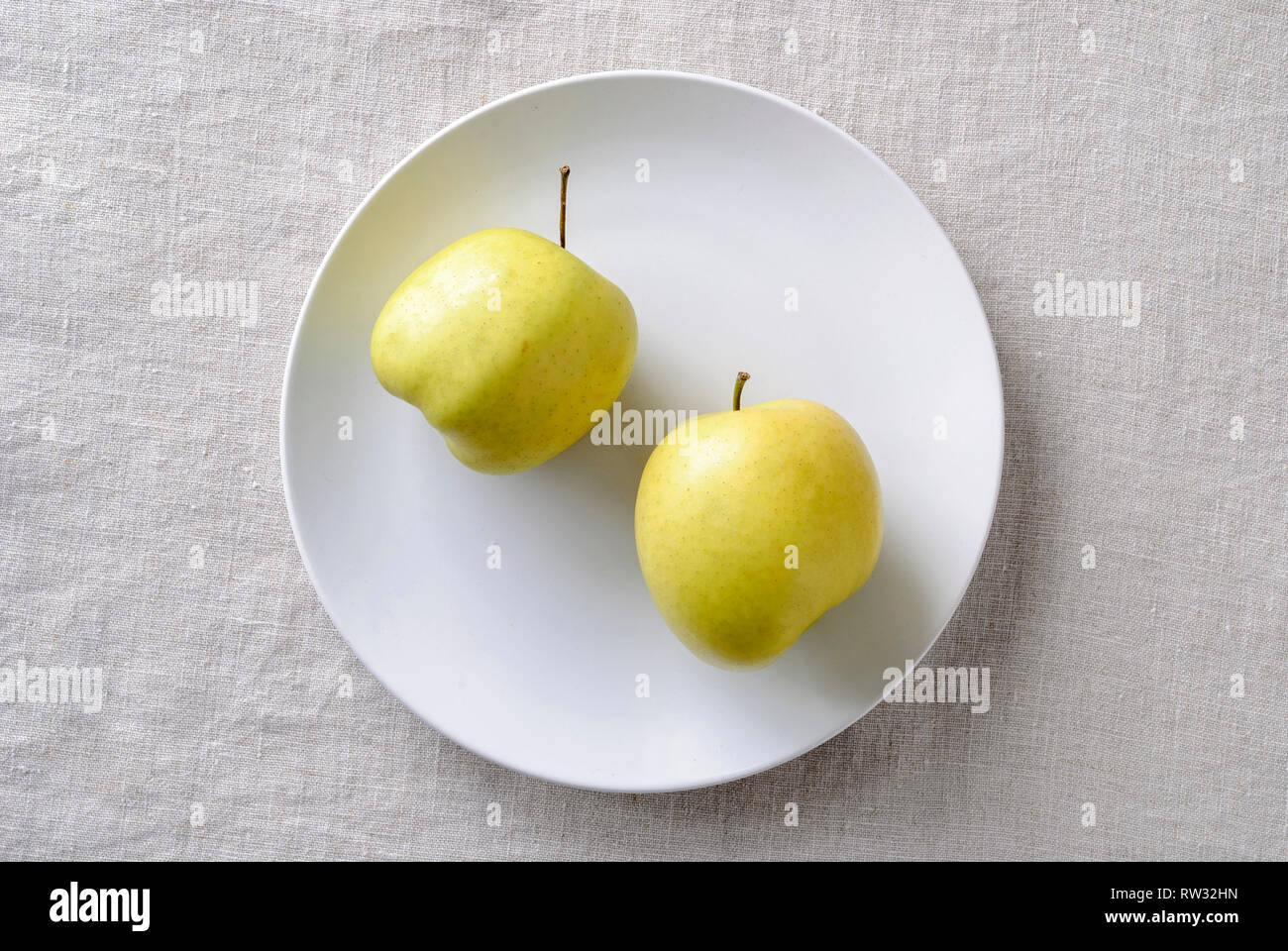 Imperfect ugly misshapen fresh golden apples rich in vitamins served on a plate - Stock Image