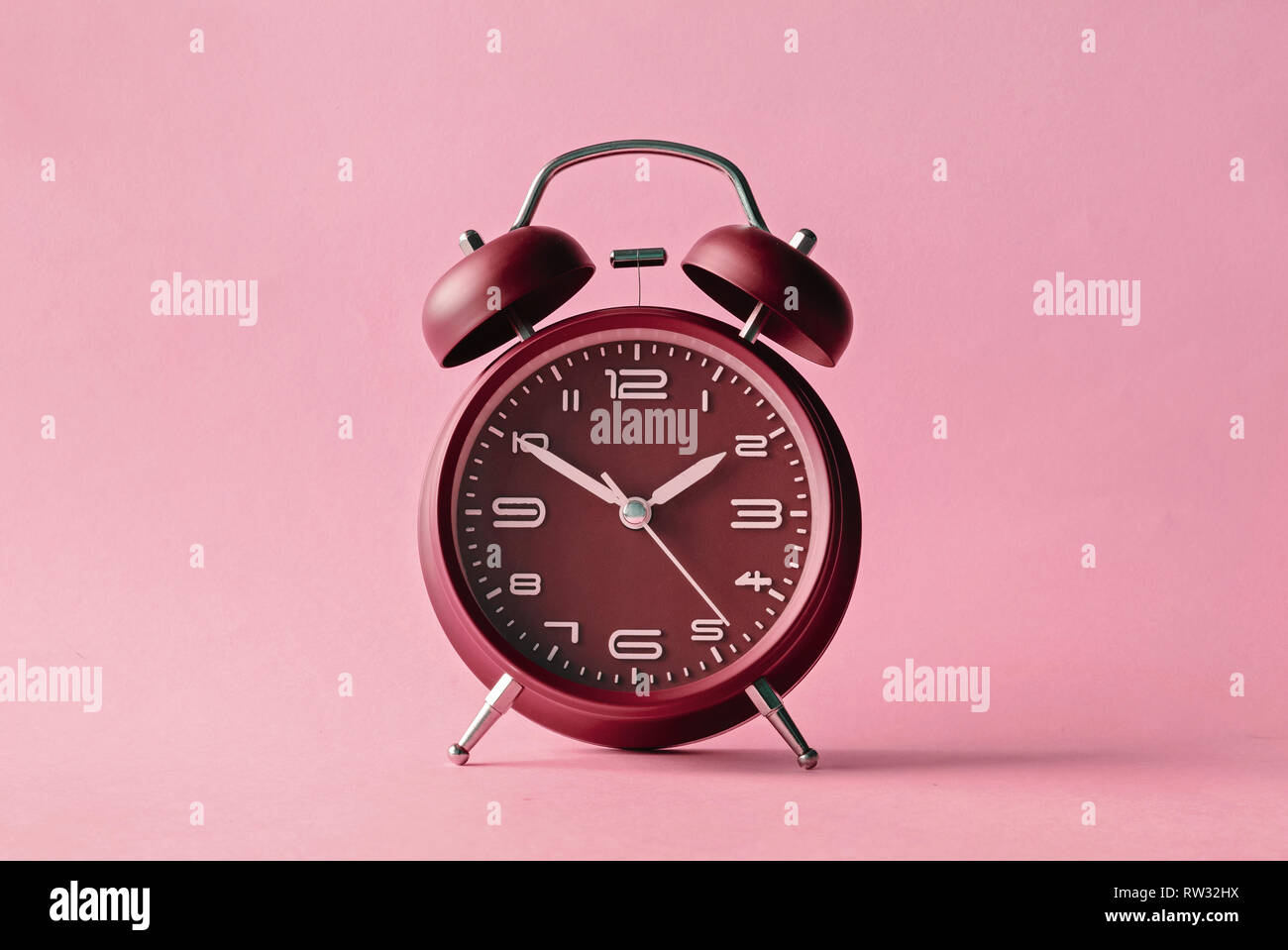 Old fashioned red alarm clock with bells centered over a pink background with lateral copy space - Stock Image