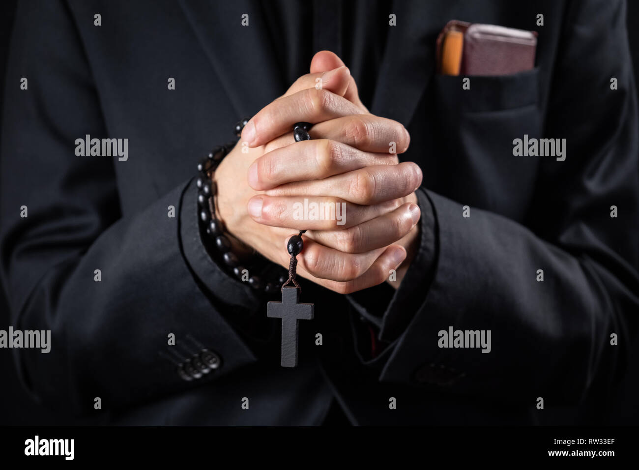 Christian person praying, low key image. Hands of a man in black suit or a priest portraying a preach Stock Photo