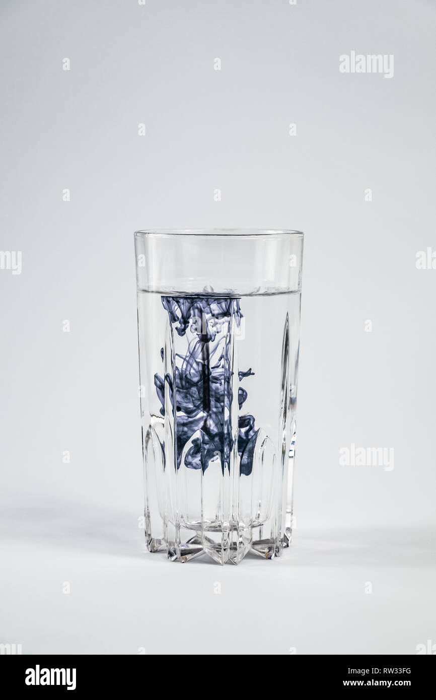 Water pollution concept. Dark substance contaminating clean water in a glass in white background - Stock Image