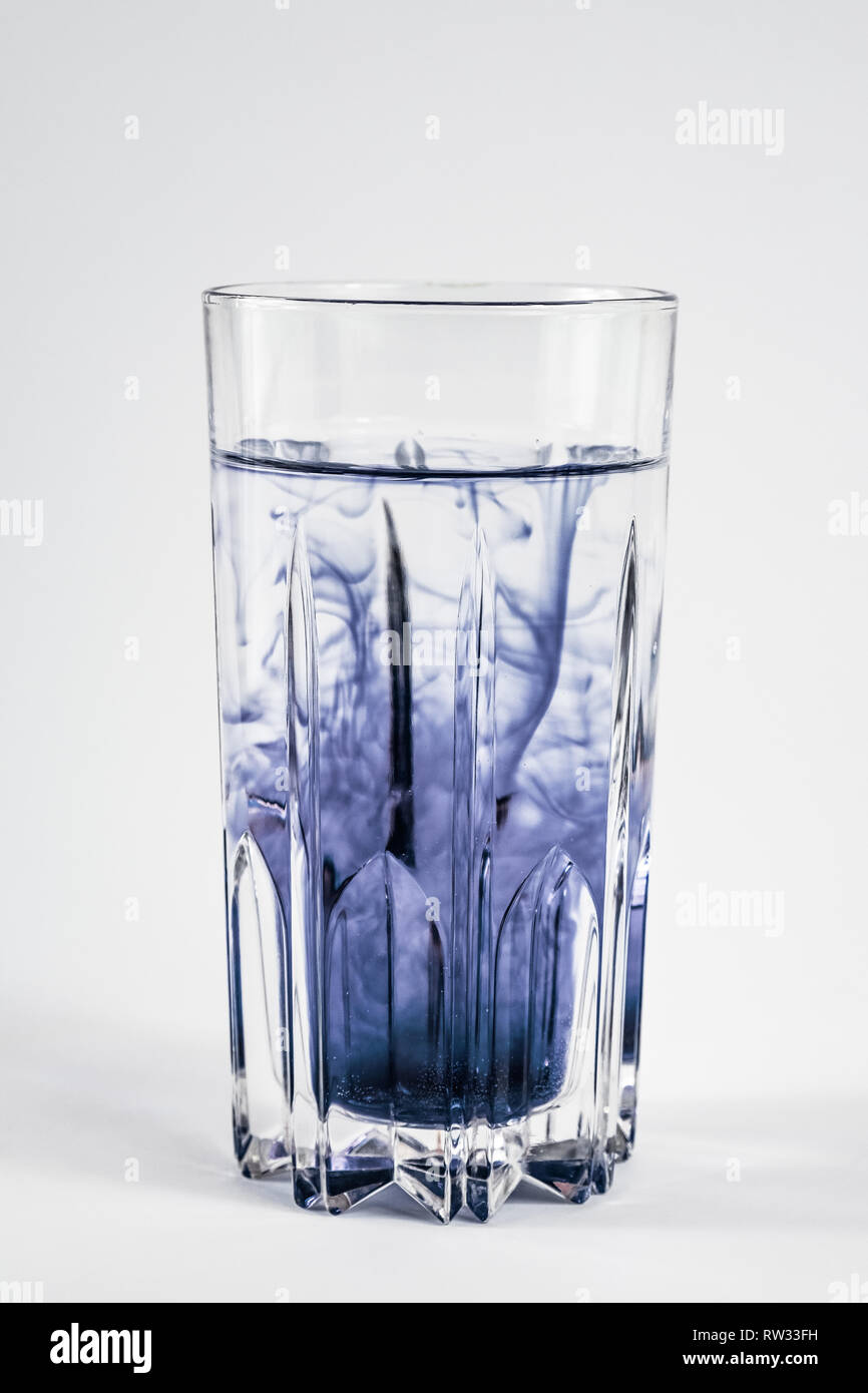 Water pollution concept. Dark substance mixing with clean water in a glass in white background - Stock Image