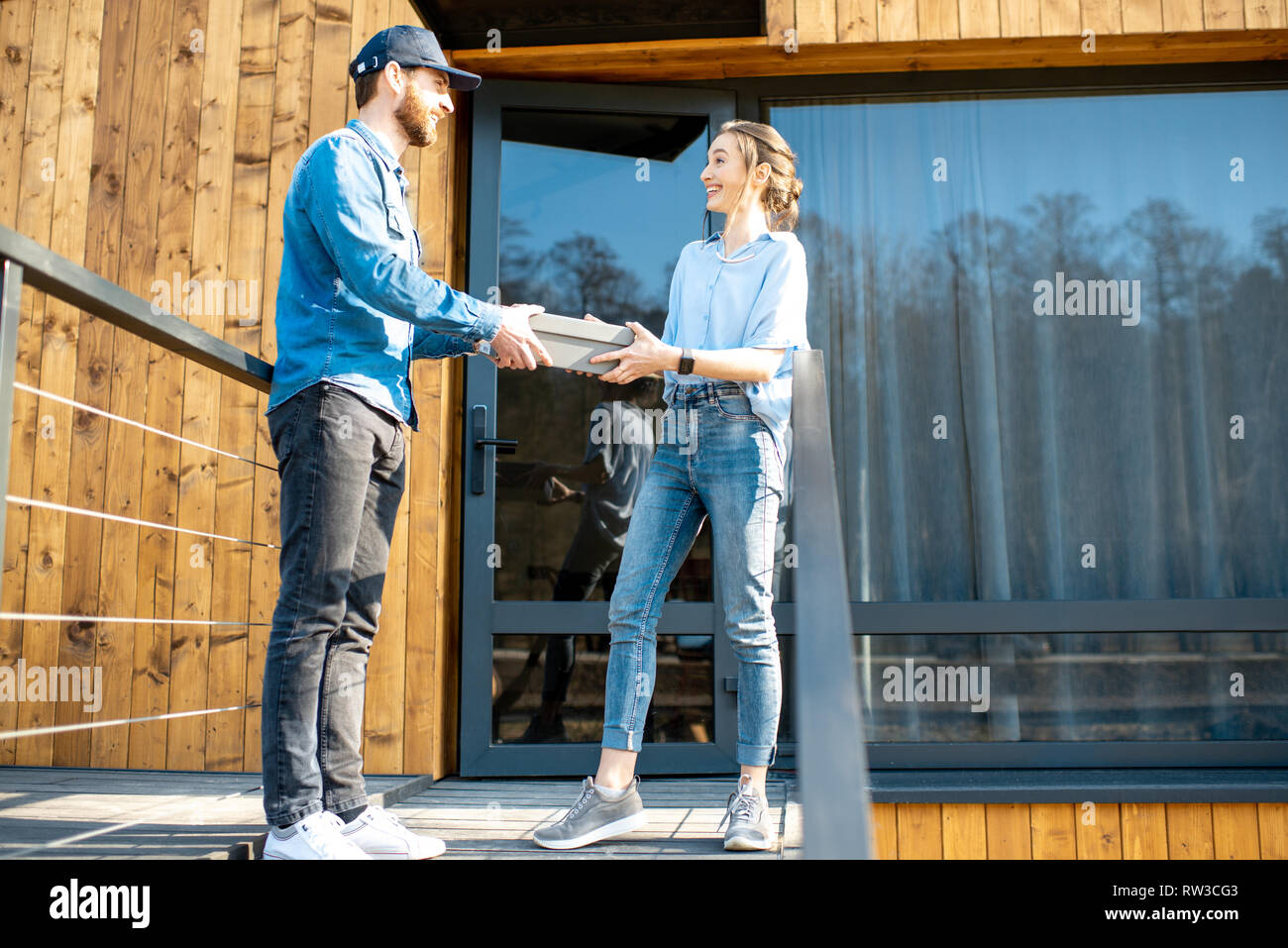 Delivery man bringing shoes home to a young woman client. Buying clothes online and delivery concept Stock Photo