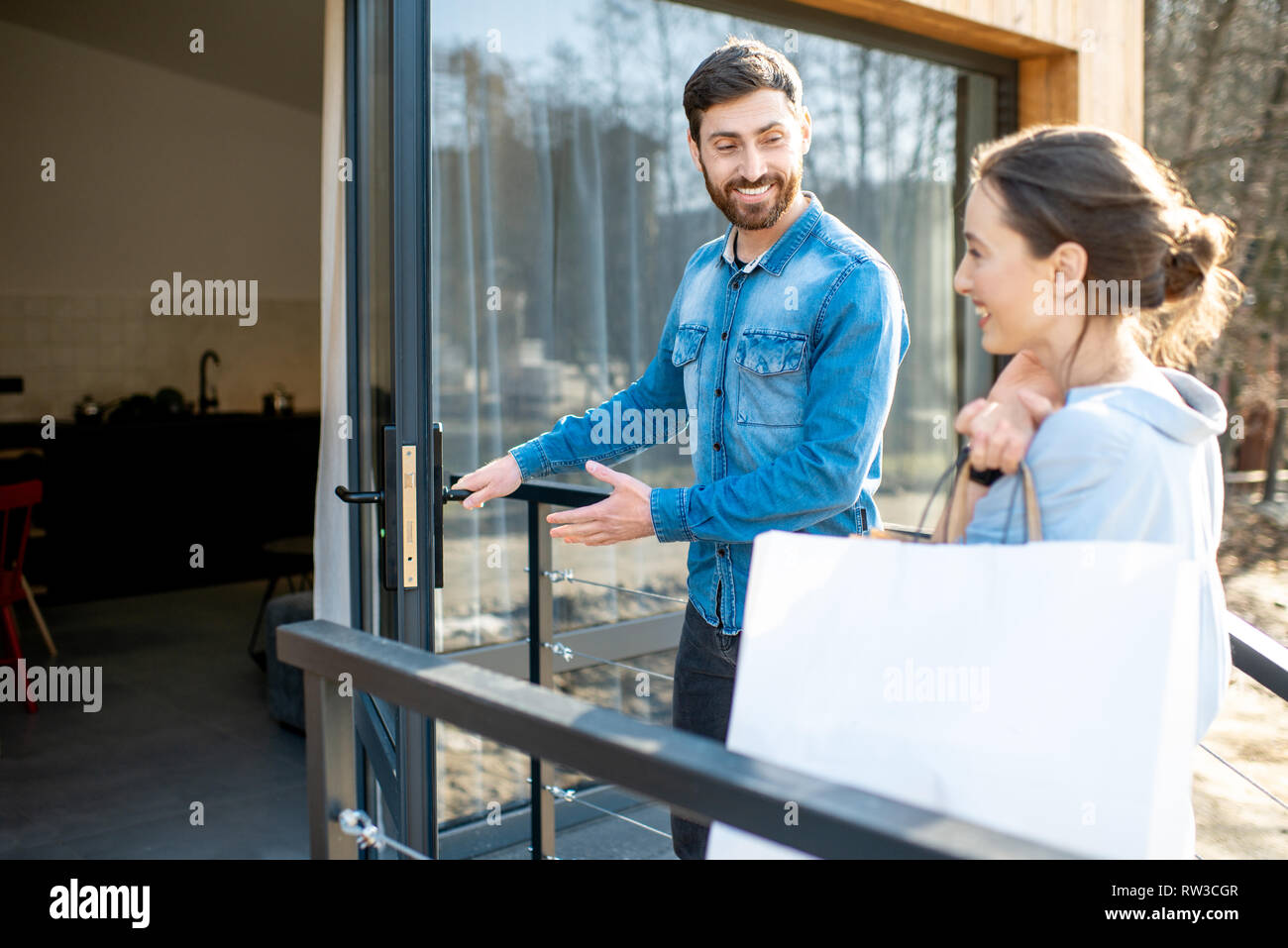 Young couple entering home carrying shopping bags. Happy purchase and modern living concept Stock Photo