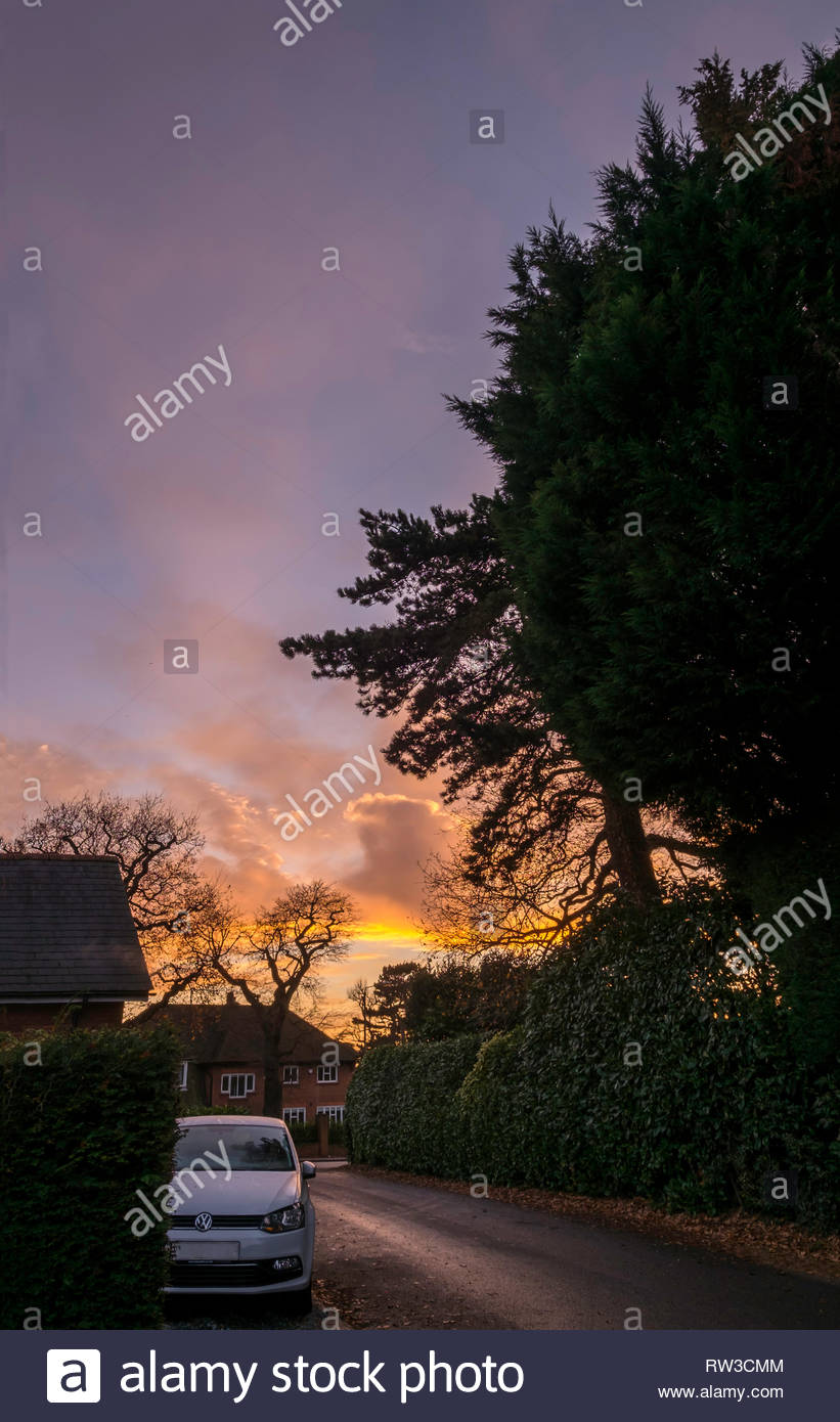 A white car parked on a road at sundown, Chislehurst, England. - Stock Image