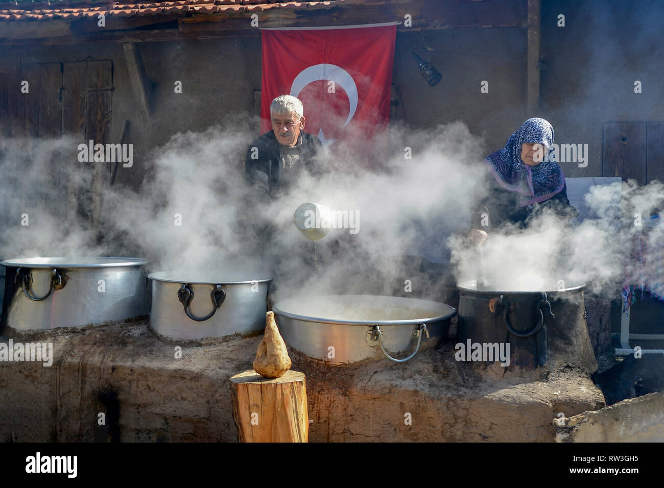 Seyitgazi,Eskisehir,TURKEY-October 15,2016: Old lady and her husband are simmering sugar beets in cauldron to make molasses. - Stock Image