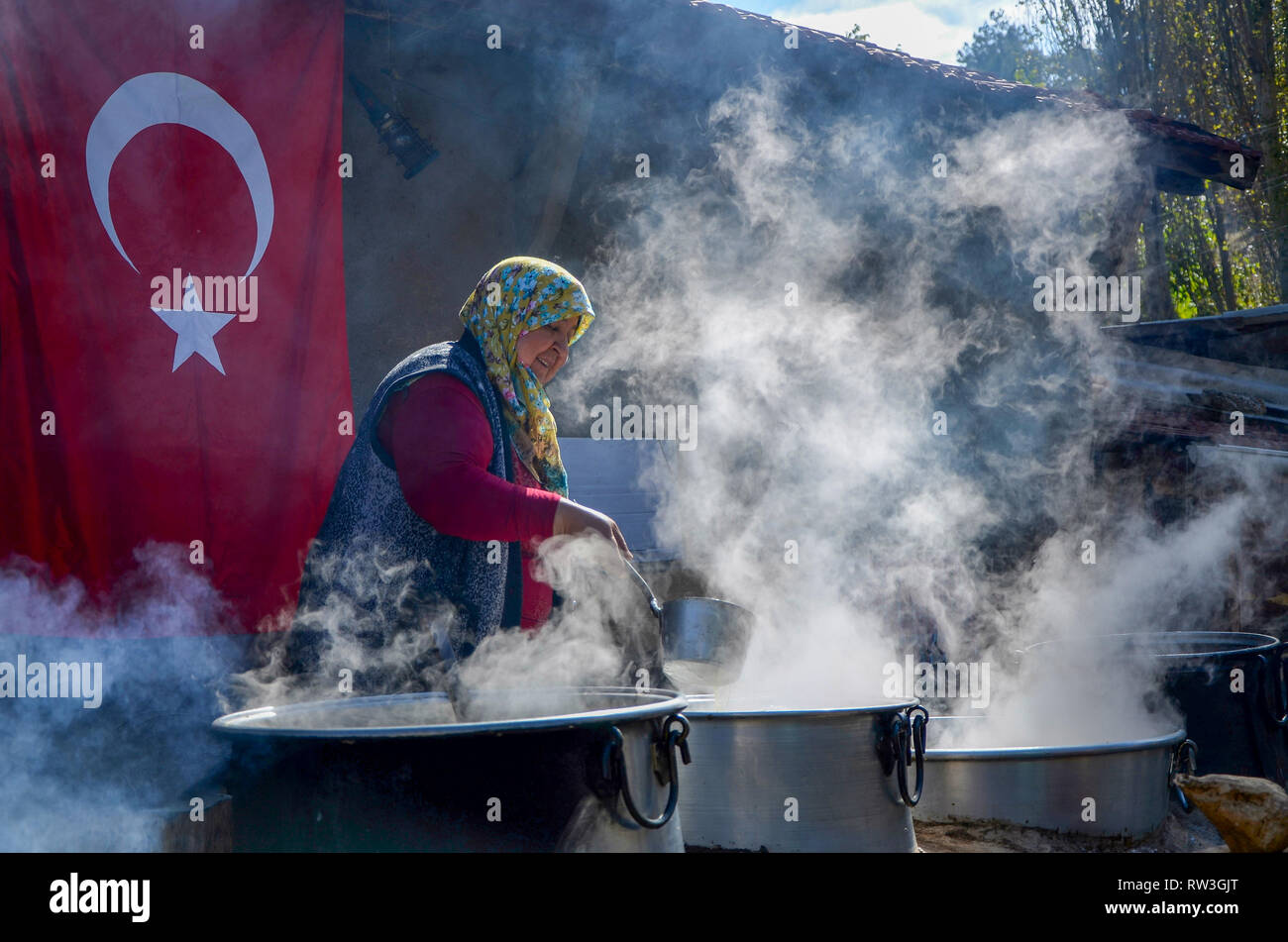 Seyitgazi,Eskisehir,TURKEY-October 15,2016: Old lady is simmering sugar beets in cauldron to make molasses. - Stock Image