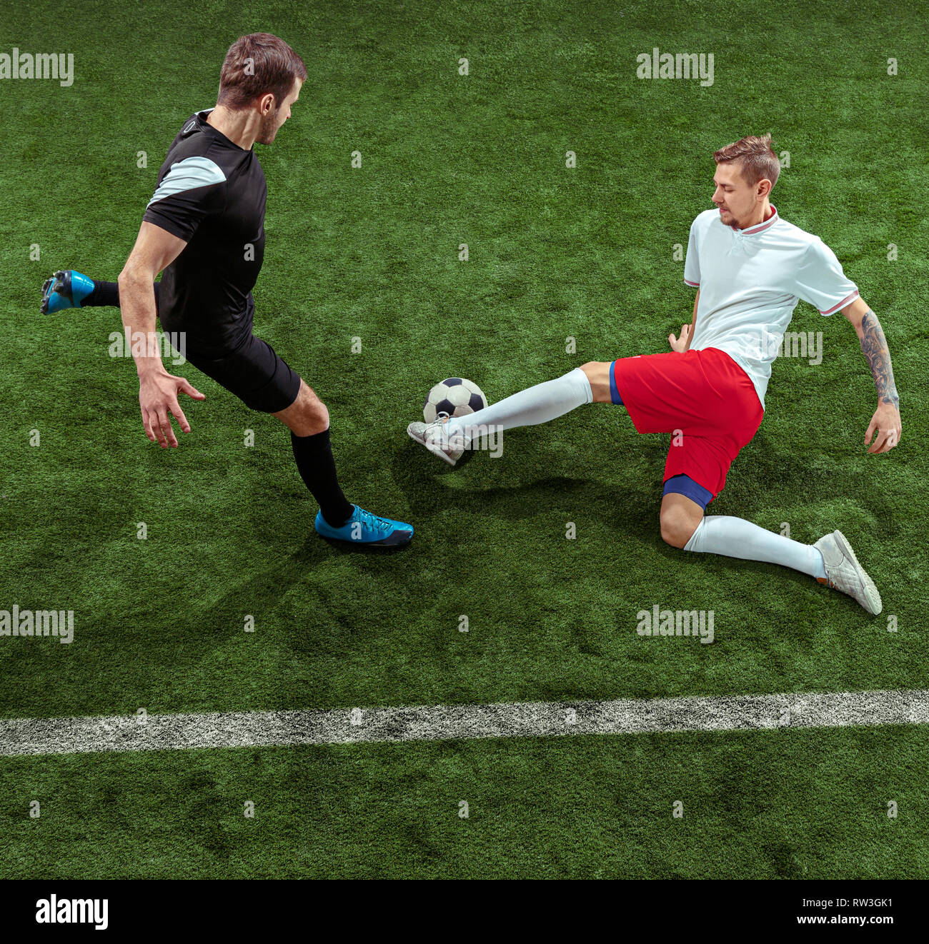 Football player tackling for ball over green grass background. Professional  male soccer players in motion at stadium. Fit jumping men in action de01619c8a1