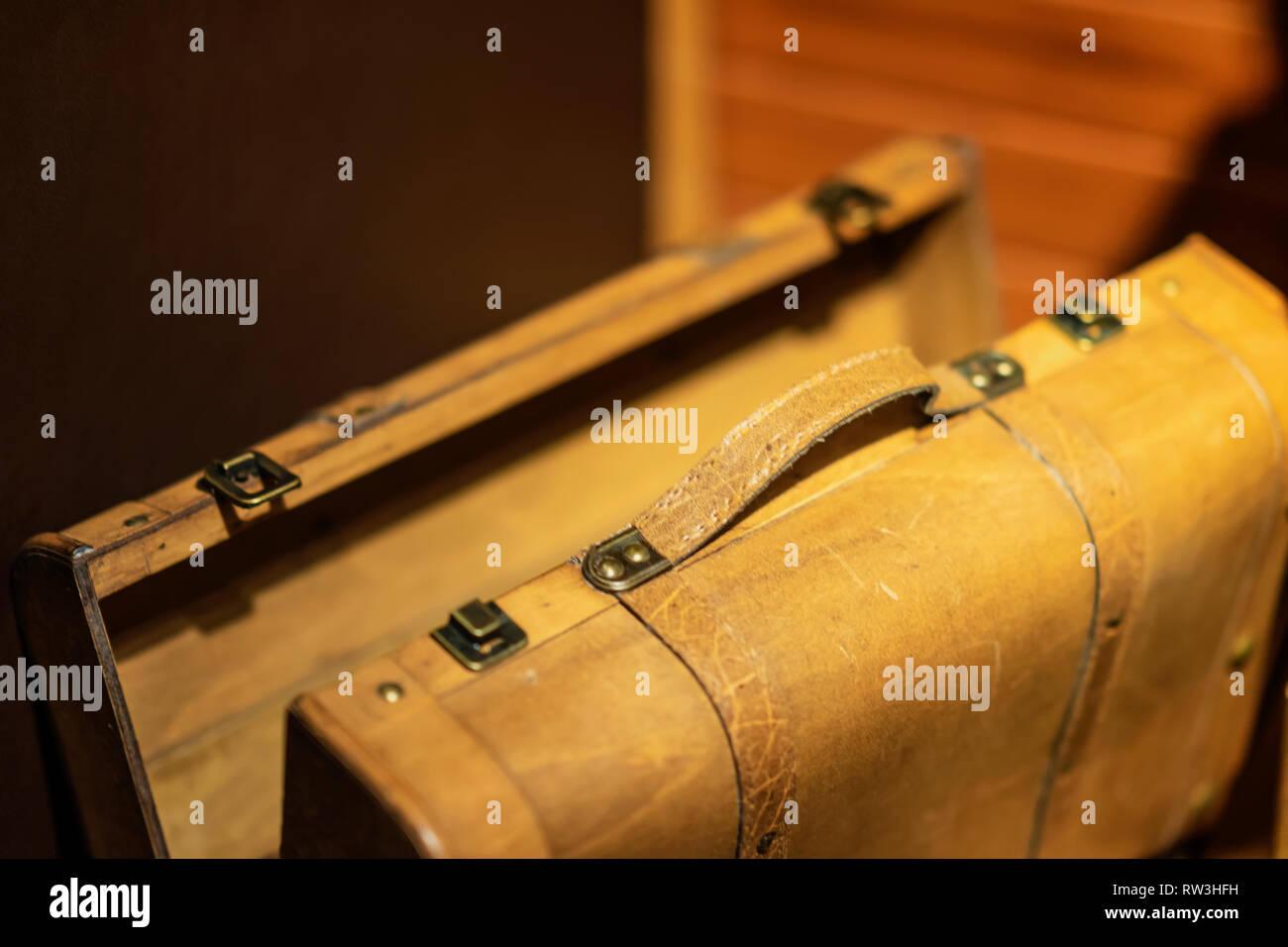 Yellow wooden suitcase for travel closeup, nostalgic luggage, vintage background - Stock Image