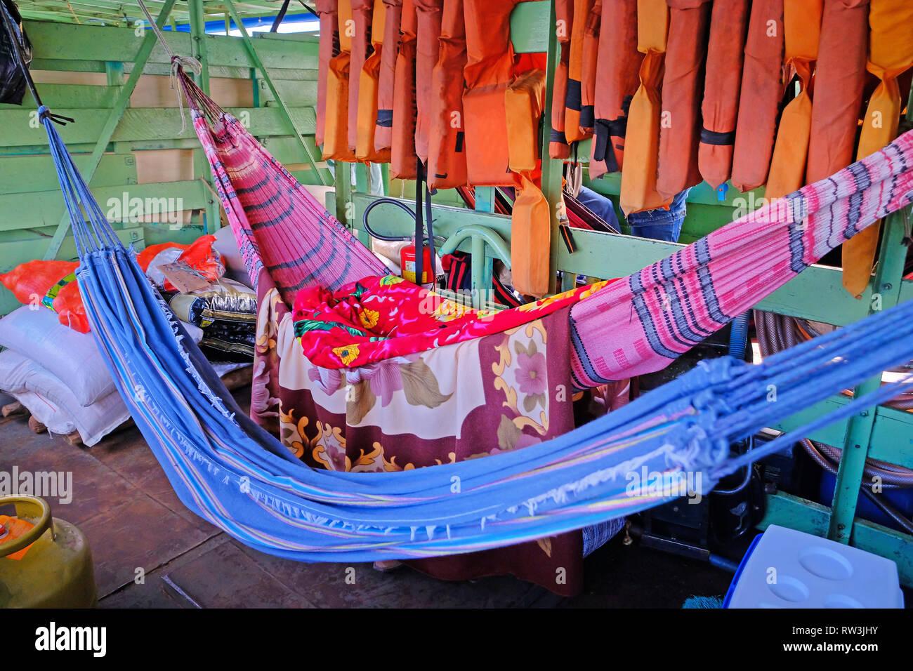 Hammocks on passengers deck on cattle pontoon boat on Rio Paraguay river, Corumba, Pantanal, Mato Grosso, Brazil - Stock Image