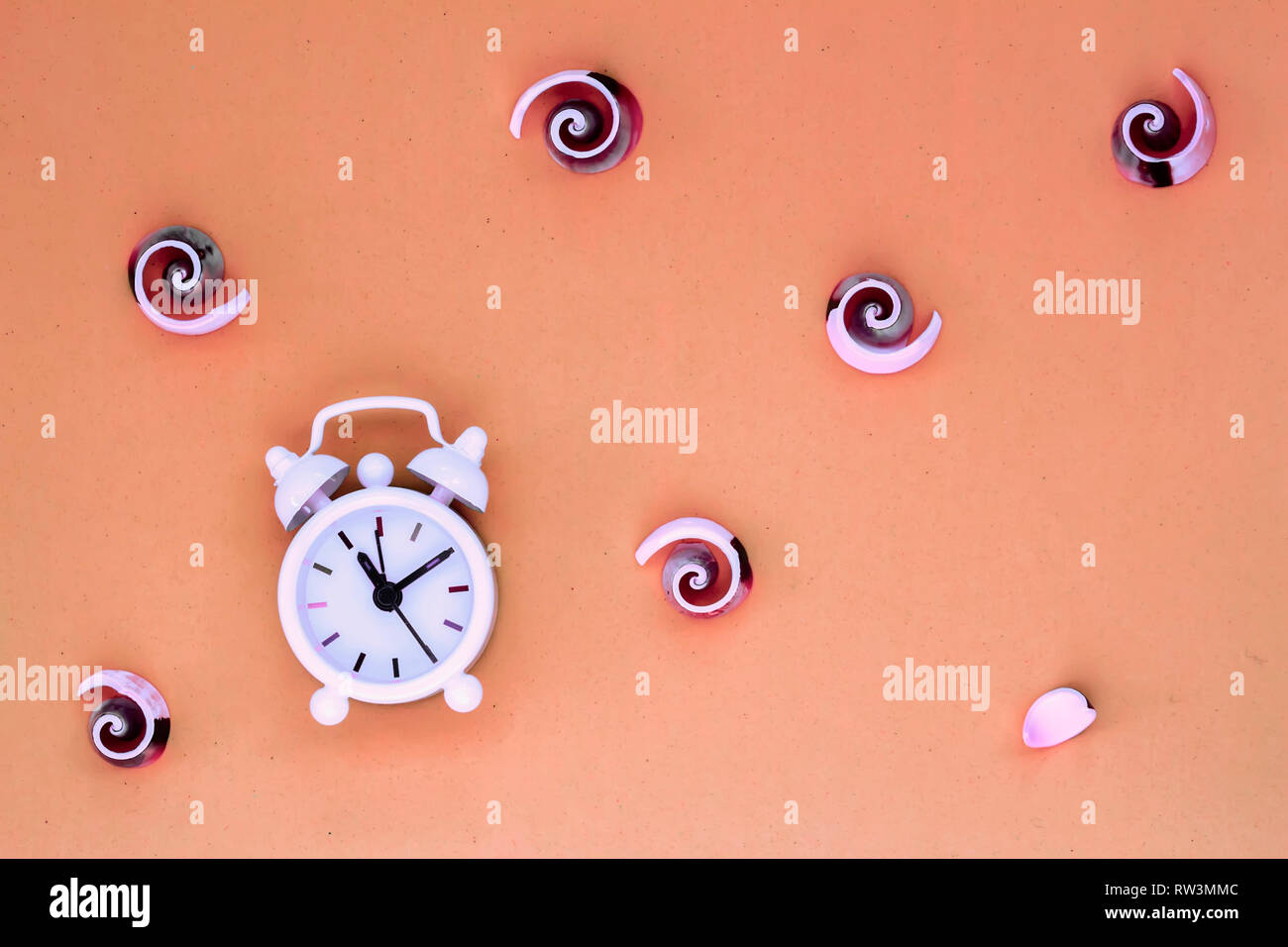 White alarm clock seashells on wooden frame. Concept of time, vacation time. Flat lay. Top view. - Stock Image