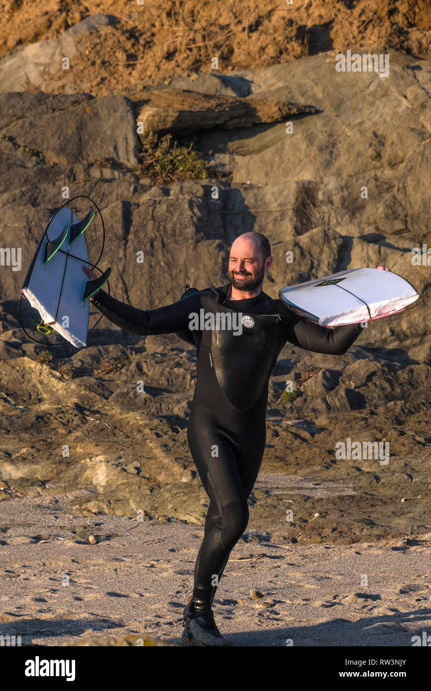 A smiling surfer standing on rocks holding up and displaying his snapped surfboard at North Fistral in Newquay Cornwall. - Stock Image