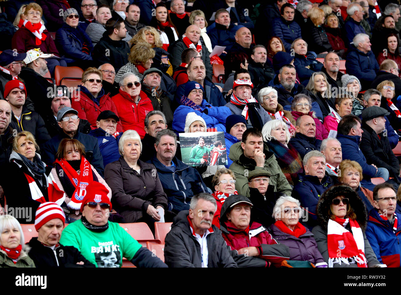 A fan in the stands holds up a photo as the funeral service for Gordon Banks is shown on the big screens at the bet365 Stadium, Stoke. - Stock Image