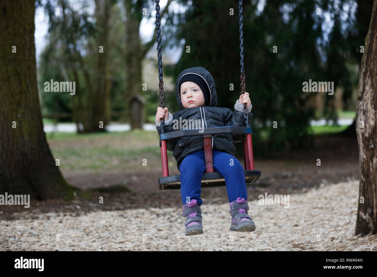 Sad, worried little boy swinging by himself, left alone unattended, looking for parents. Childhood, parenting, neglect and emotions concept. - Stock Image