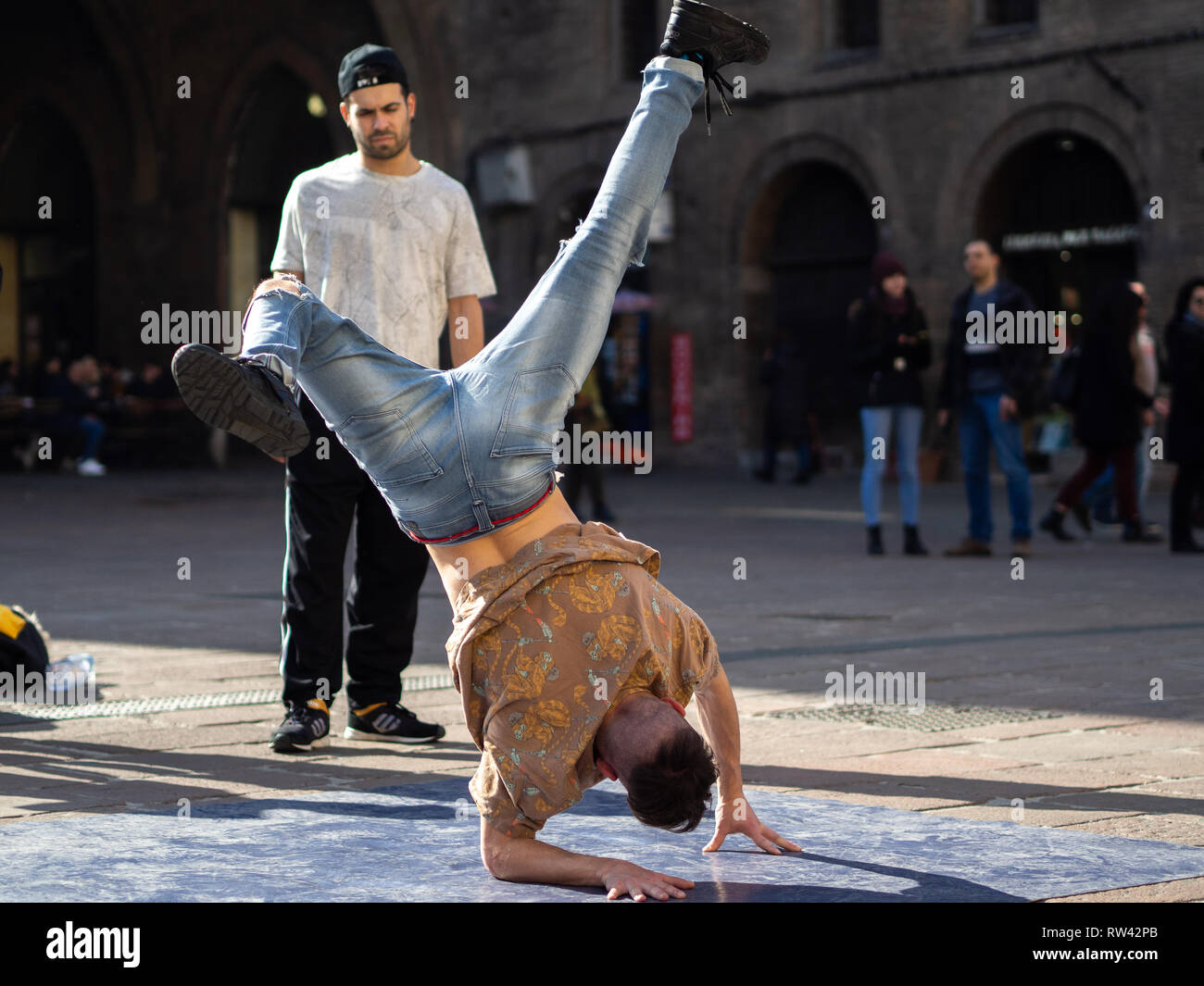February, 16 2019 Bologna, Italy. Some boys dance break dance in the middle of a street in Bologna, Italy and in front of a church. Stock Photo