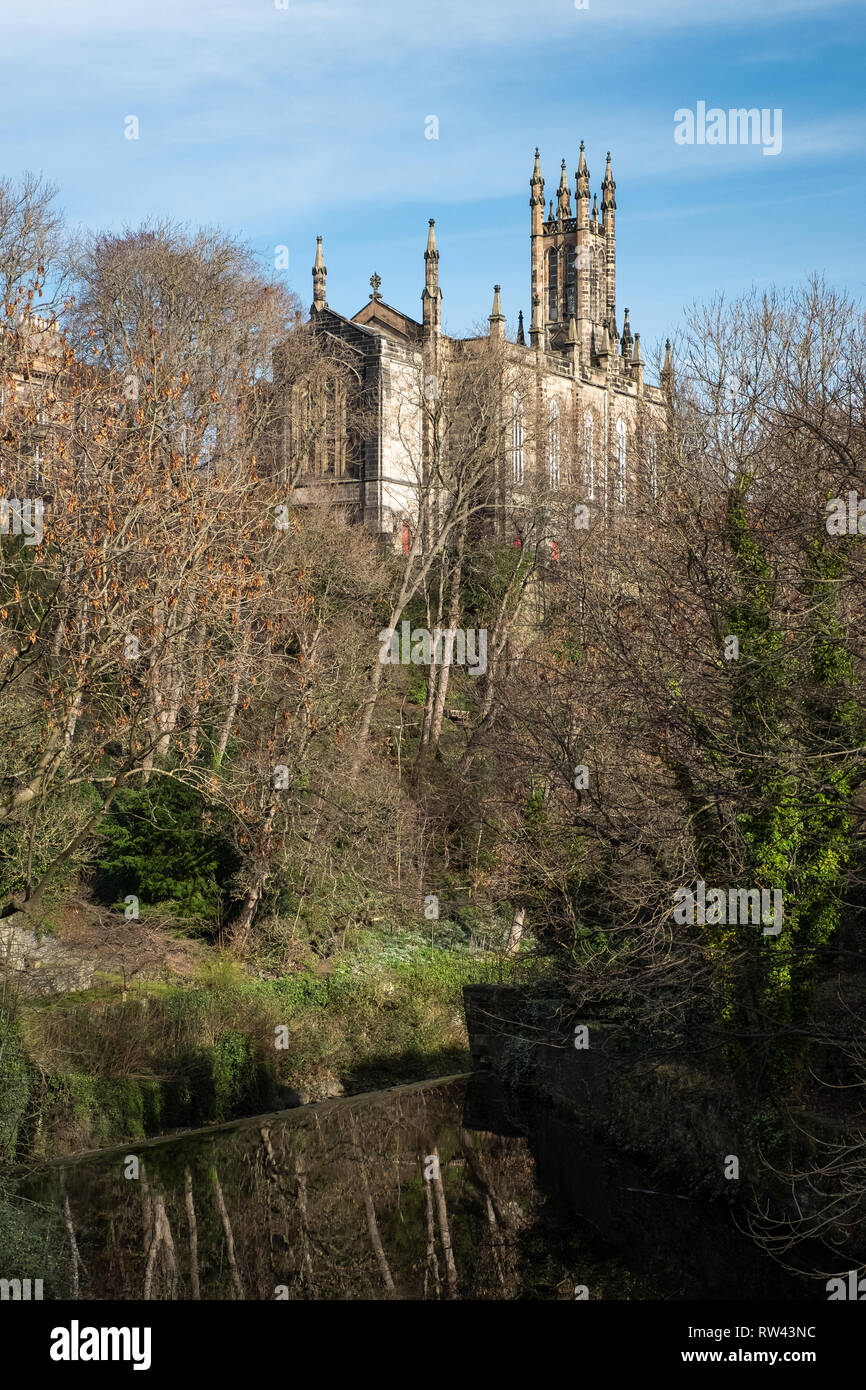 The Rhema Christian Centre Church viewed between the trees from Dean Village on a sunny day in Edinburgh, Scotland - Stock Image