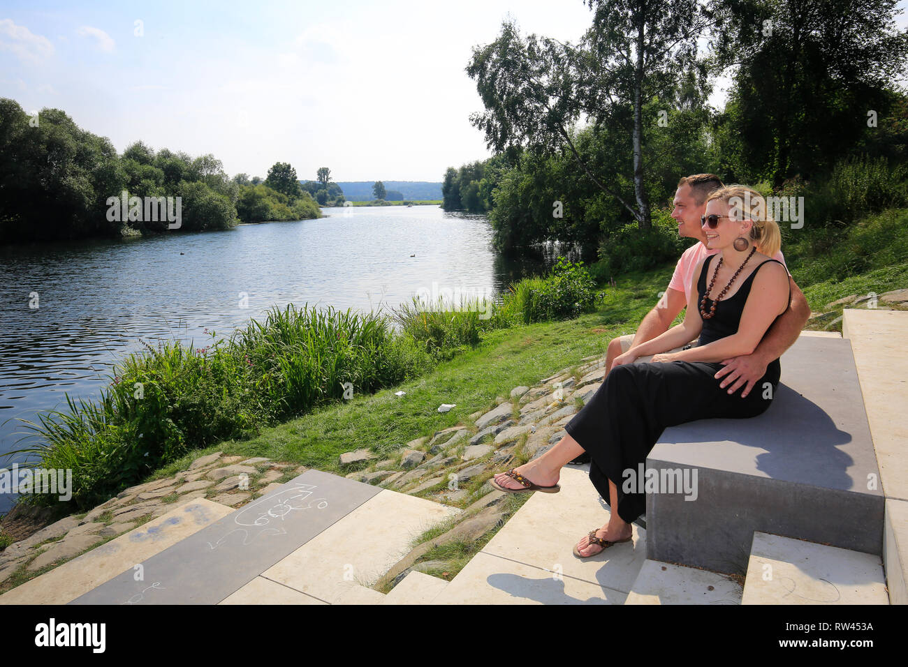 Essen, North Rhine-Westphalia, Ruhr area, Germany, Ruhr in the district of Steele, a young couple sits on the banks of the Ruhr, photographed on the o - Stock Image