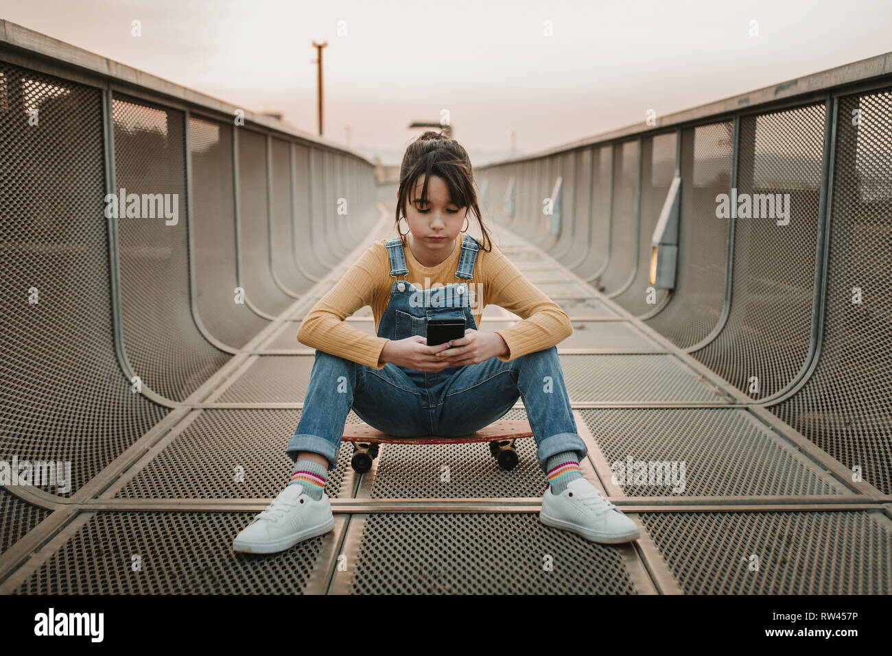 Stylish teen in jean overall sitting on skateboard and using mobile phone on footpath in city - Stock Image