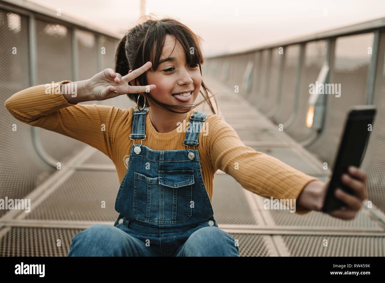 Funny girl taking selfie on smartphone on walkway - Stock Image
