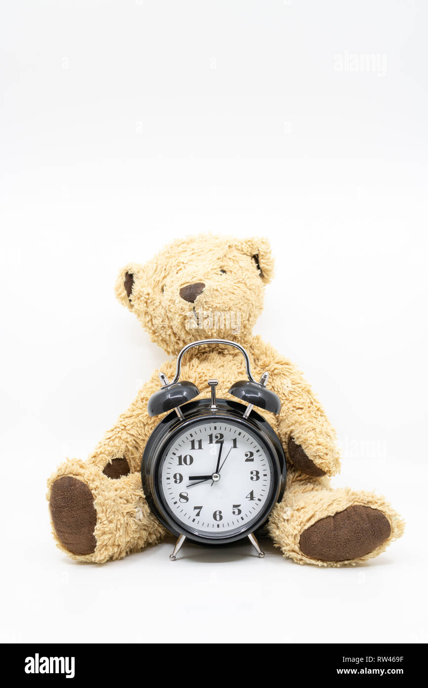 Time to go to bed concept with clock and teddy bear - Stock Image