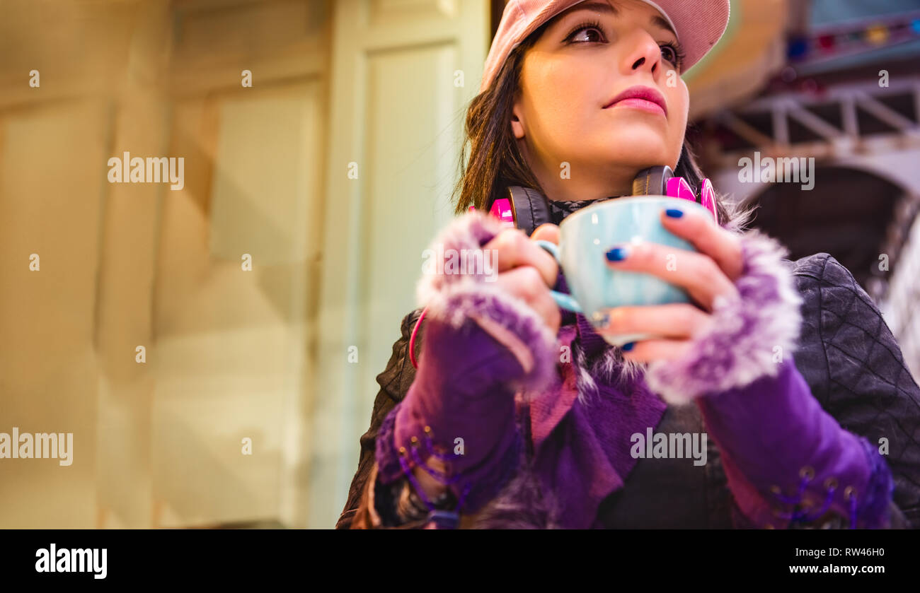 Close up portrait of a cute woman with coffee cup in warm clothing,cap and headphones sits at local shop - Stock Image