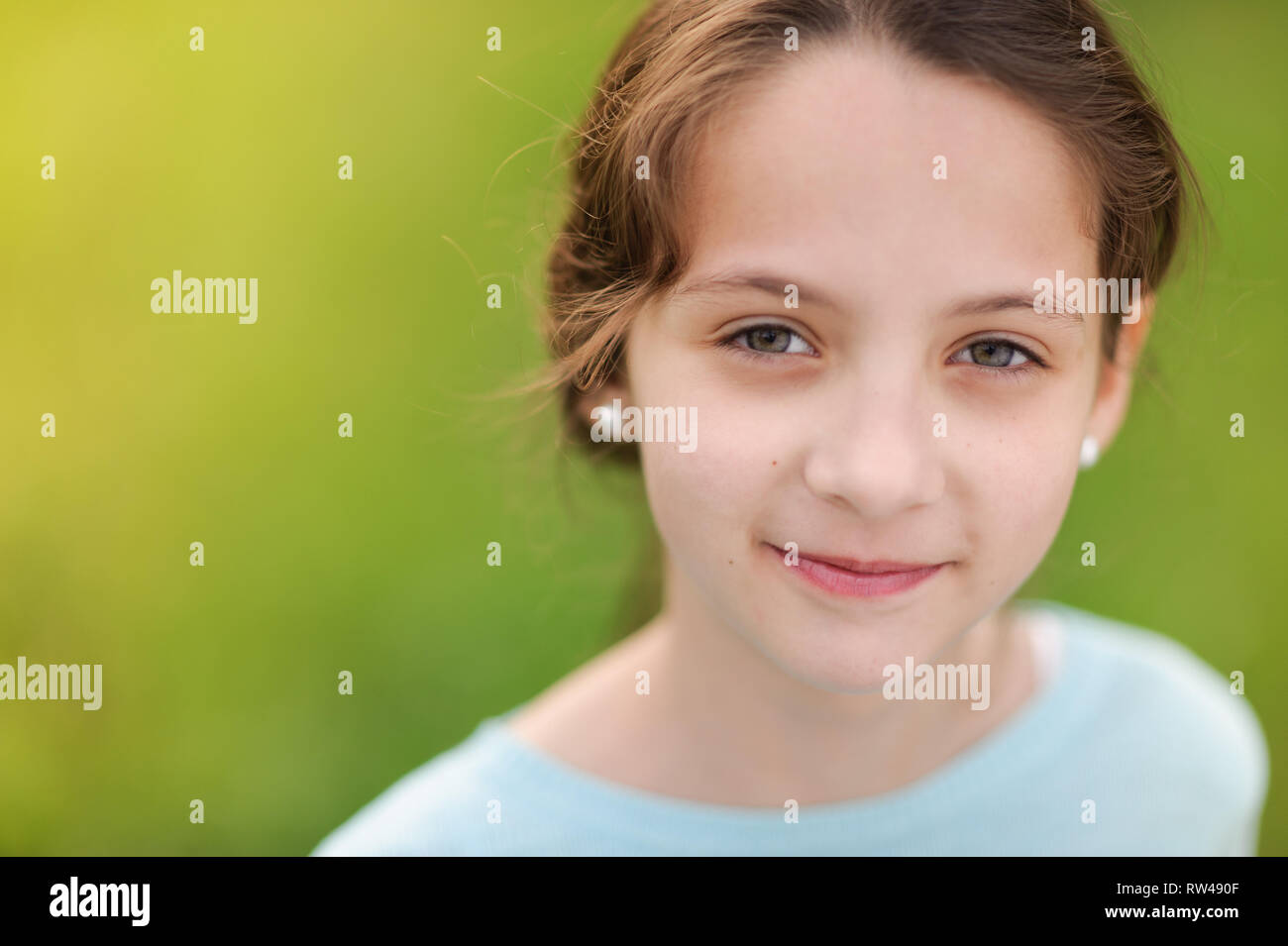 closeup portrait of happy smiling little caucasian girl in earrings and blue blouse on warm green background Stock Photo