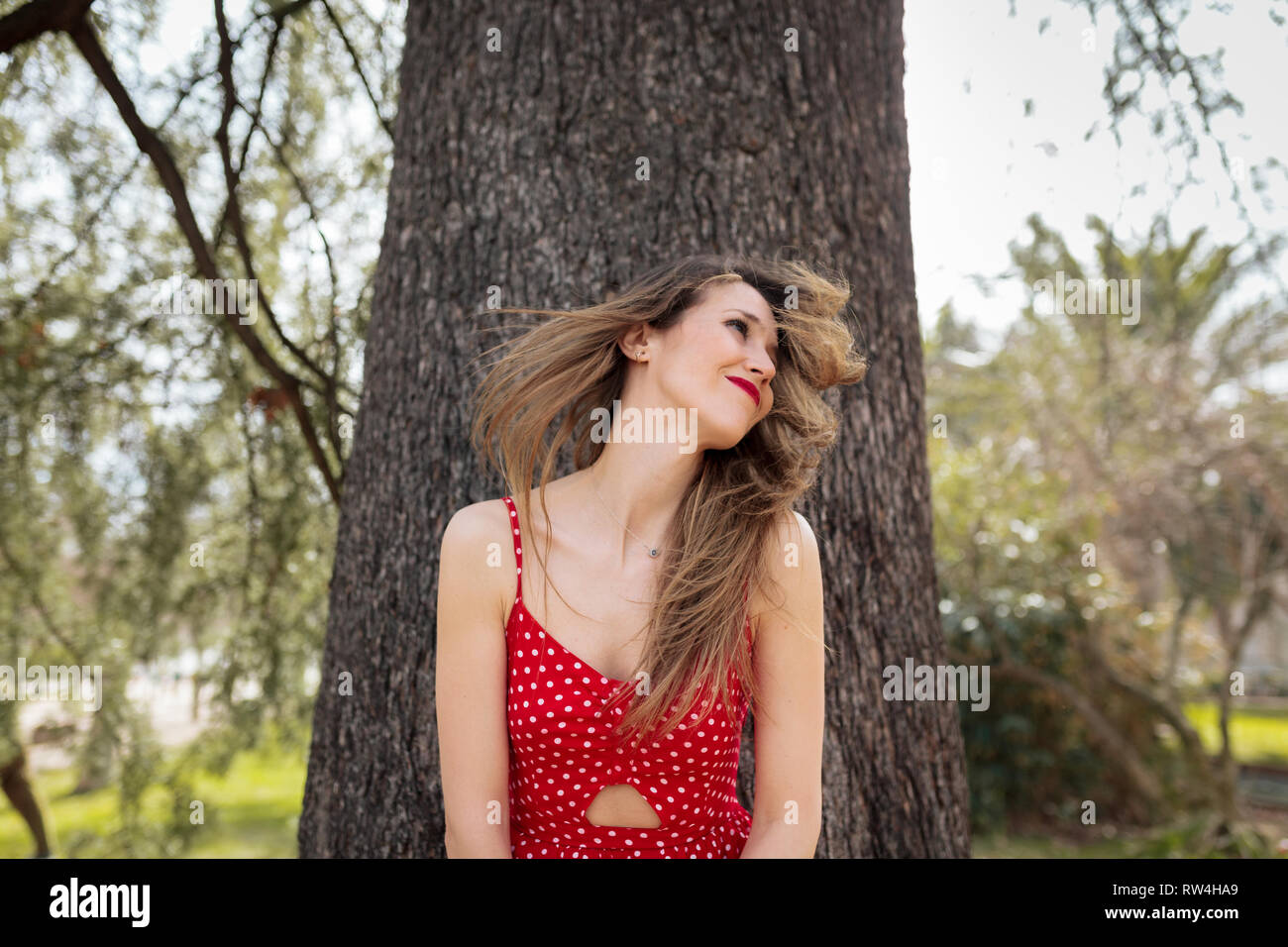 Young smiling blond woman with red dress moving her hair Stock Photo